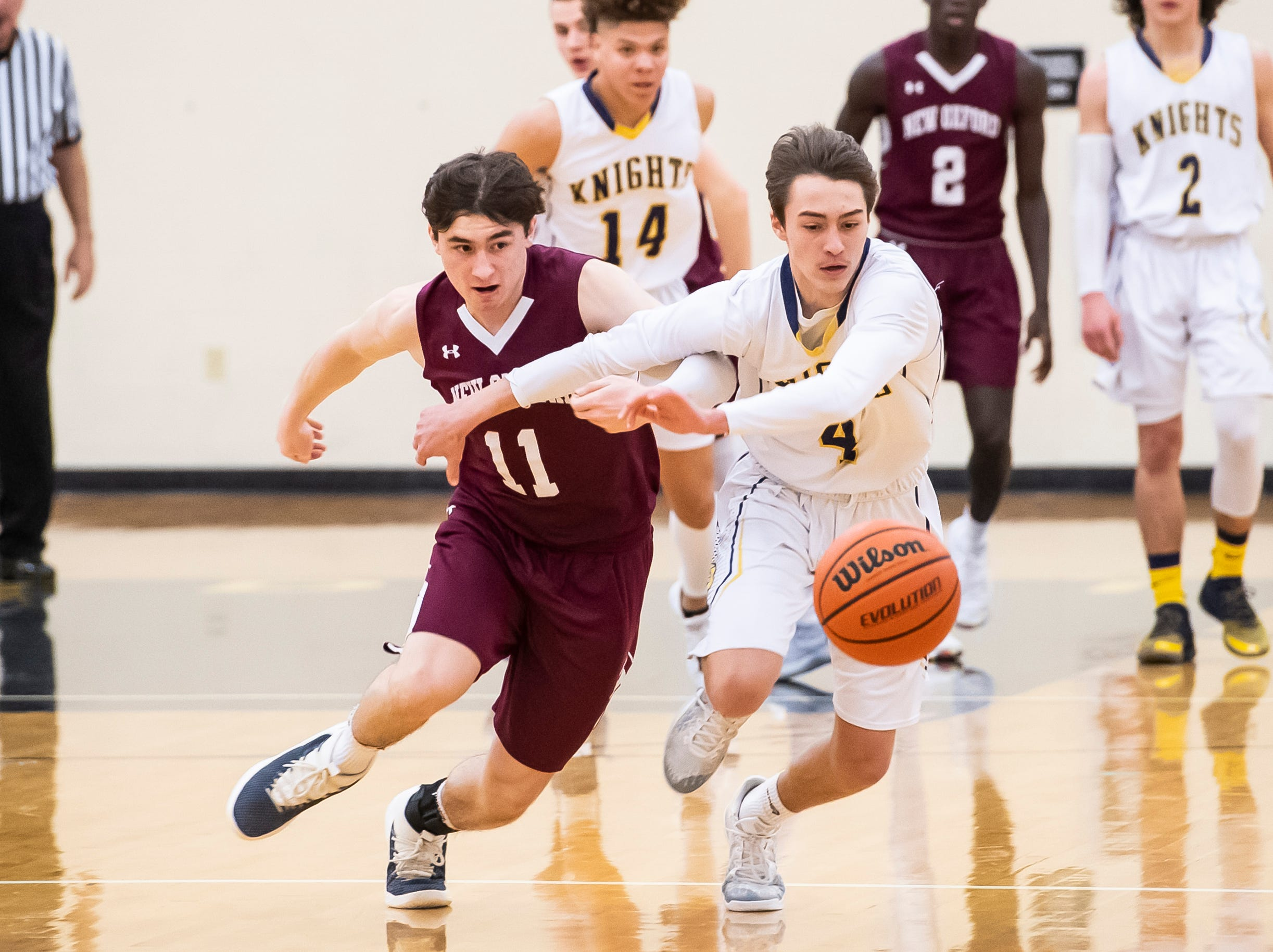 """Eastern York's Trevor Seitz (4) and New Oxford's Noah Strausbaugh chase after a loose ball during play in a YAIAA quarterfinal game at Red Lion High School Saturday, February 9, 2019. """"I thought that (Strausbaugh) and Cameron (Krebs) collectively really tried to make Seitz really, really work and wear him down a little bit,"""" New Oxford head coach Sean Bair said."""
