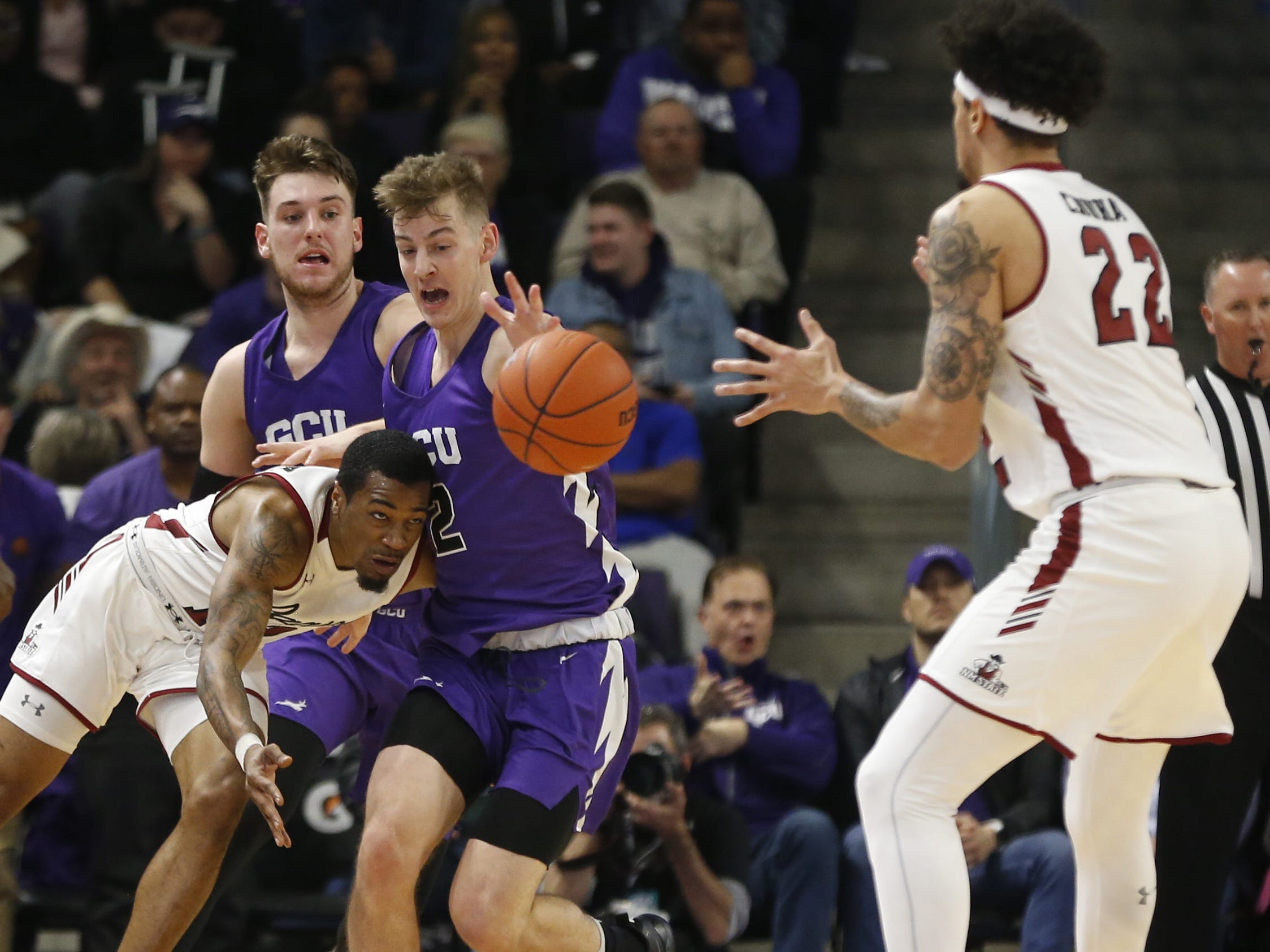 New Mexico State's AJ Harris (12) passes the ball under pressure from GCU's Trey Dreschel (2) during the first half at Grand Canyon University Arena in Phoenix, Ariz. on February 9, 2019.
