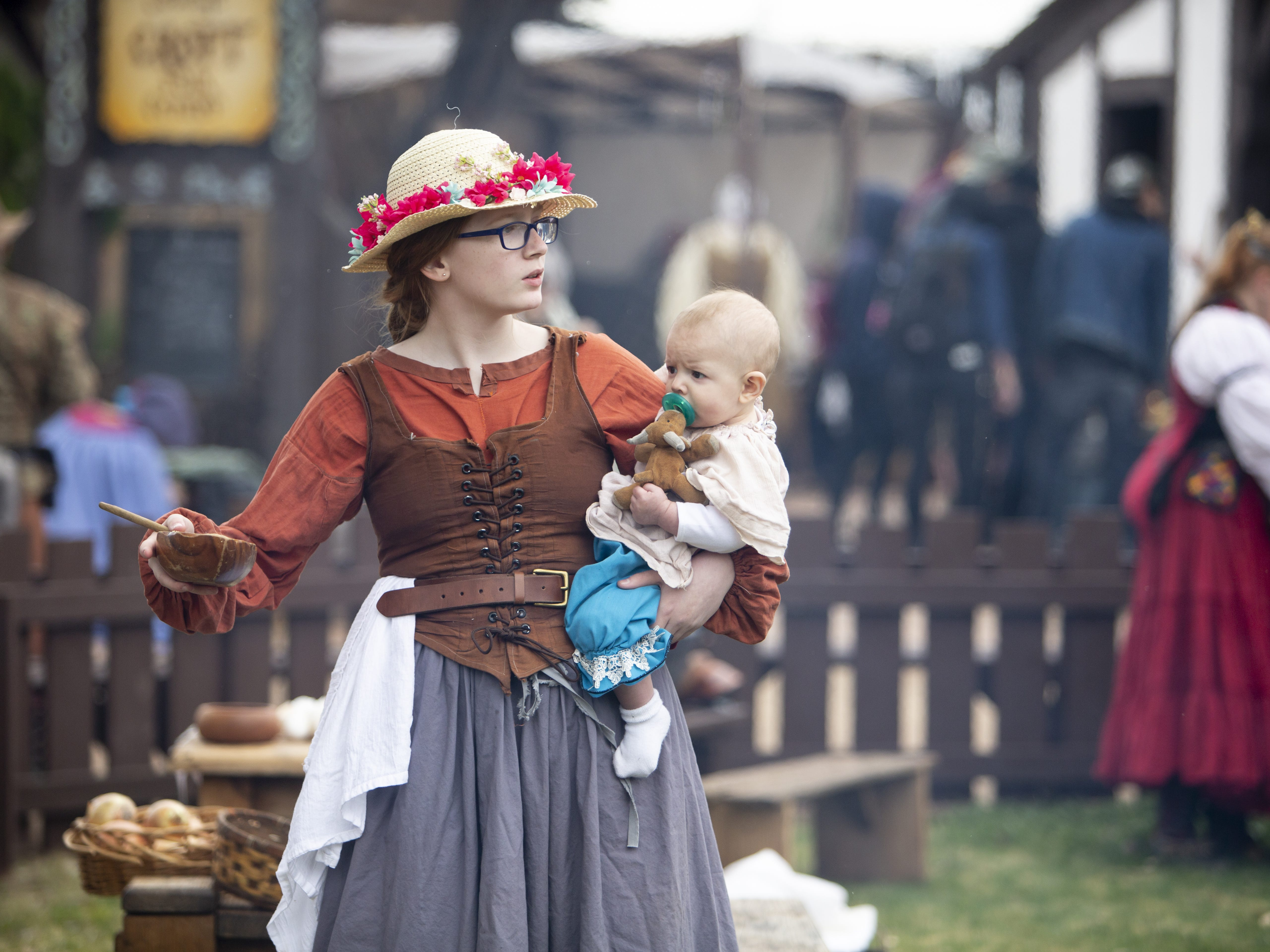 Alyssa Wood helps take care of a 6-month-old baby whose mother is also participating in the Arizona Renaissance Festival 2019 on Feb. 9, 2019 in Gold Canyon, Ariz.