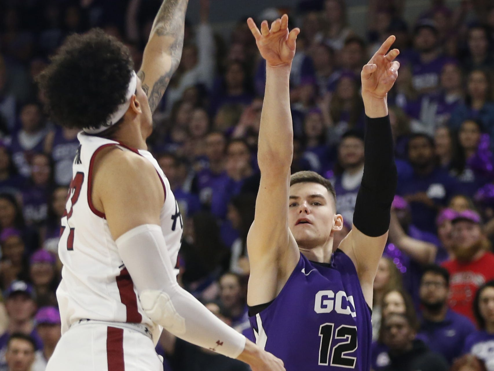 GCU's Roberts Blumbergs (12) shoots against New Mexico State's Eli Chuha (22) during the first half at Grand Canyon University Arena in Phoenix, Ariz. on February 9, 2019.