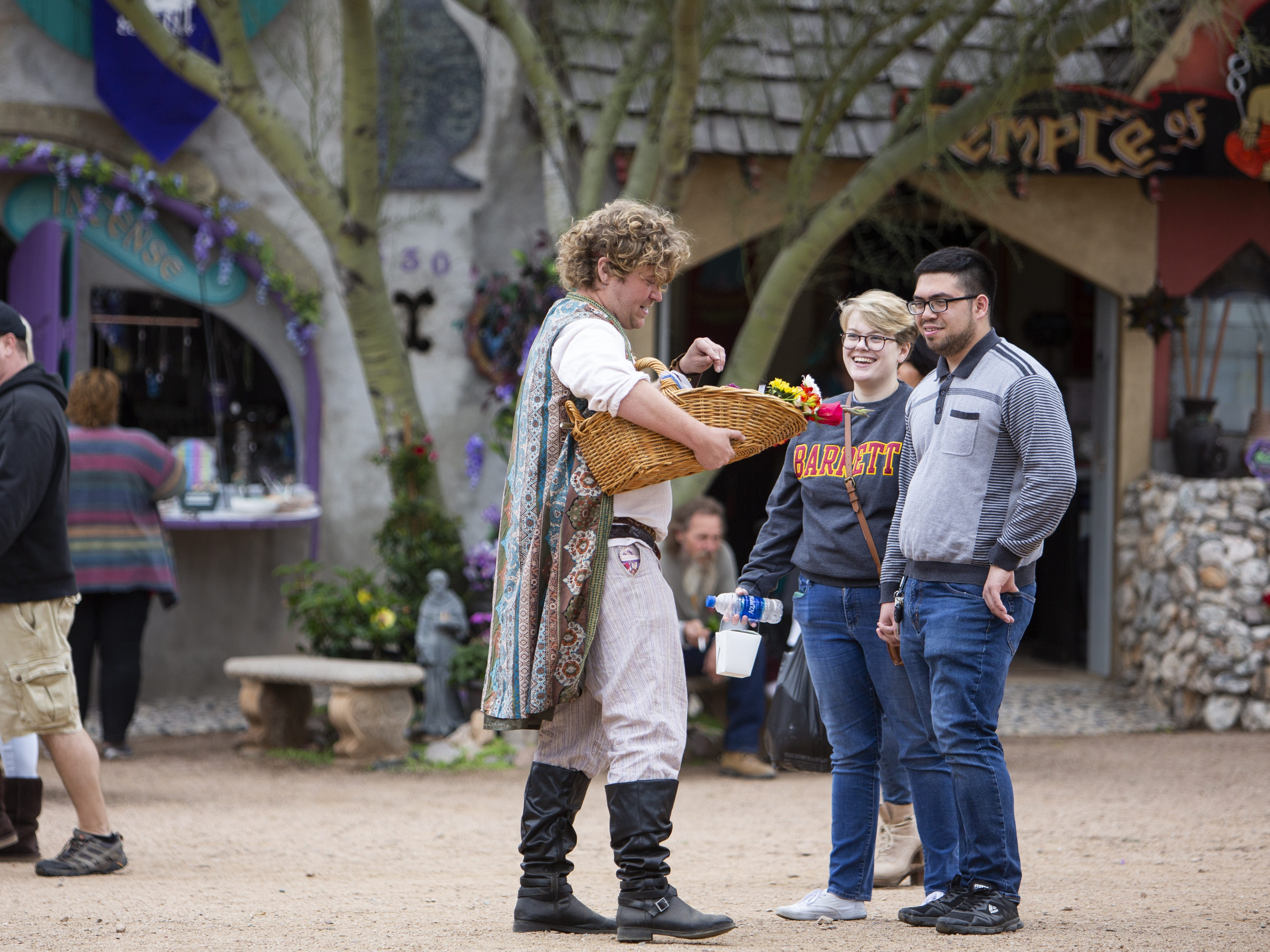 Ryan Pale, left, sells flowers to Elizabeth Carnesi and Johnny Huson, right, at the Arizona Renaissance Festival 2019 on Feb. 9, 2019 in Gold Canyon, Ariz.