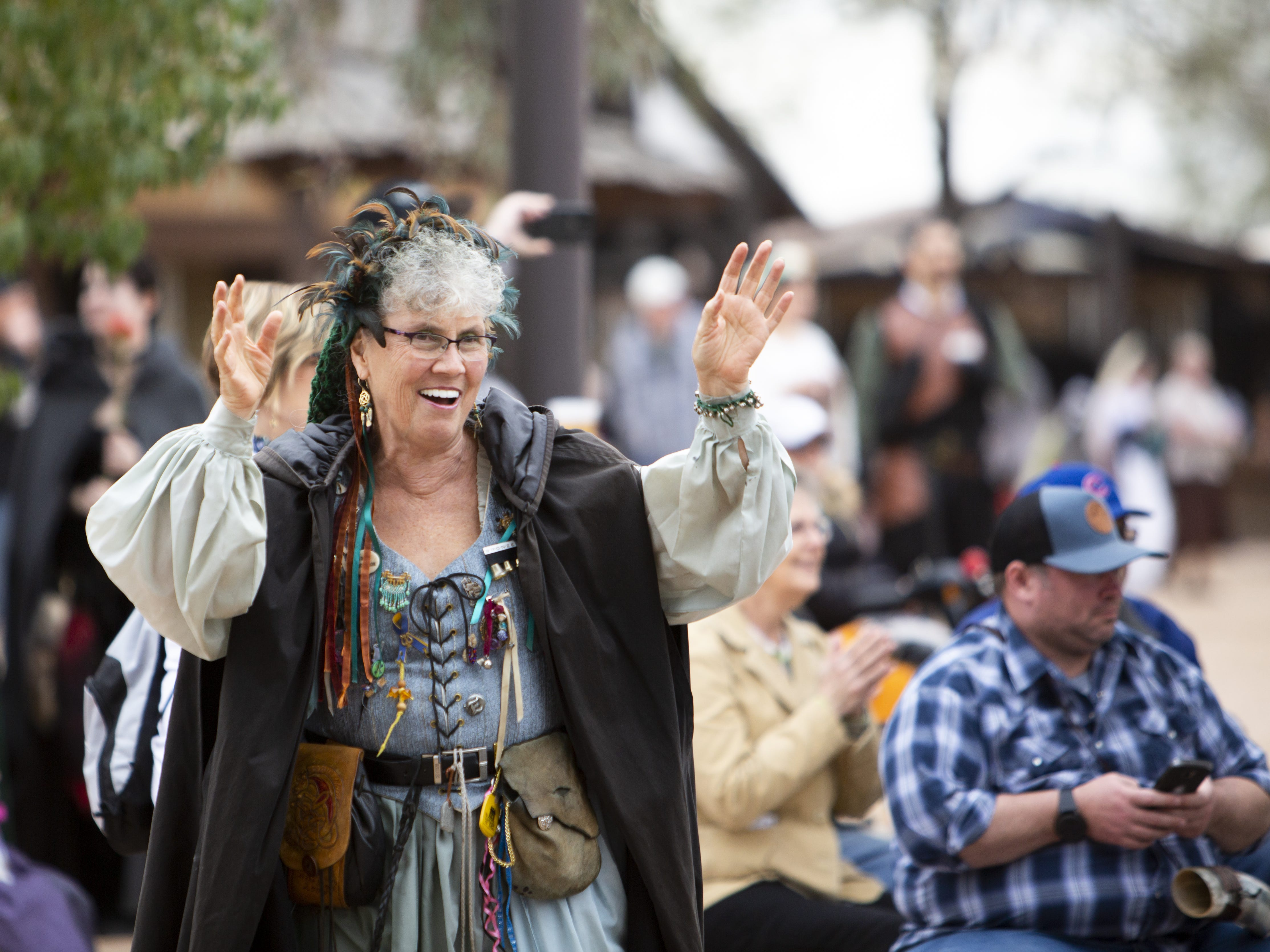 Jeannette Bonucci, who sells CDs and DVDs for performers by the stage, dances along to the Cast in Bronze performance by Frank DellaPenna at the Arizona Renaissance Festival 2019 on Feb. 9, 2019 in Gold Canyon, Ariz.