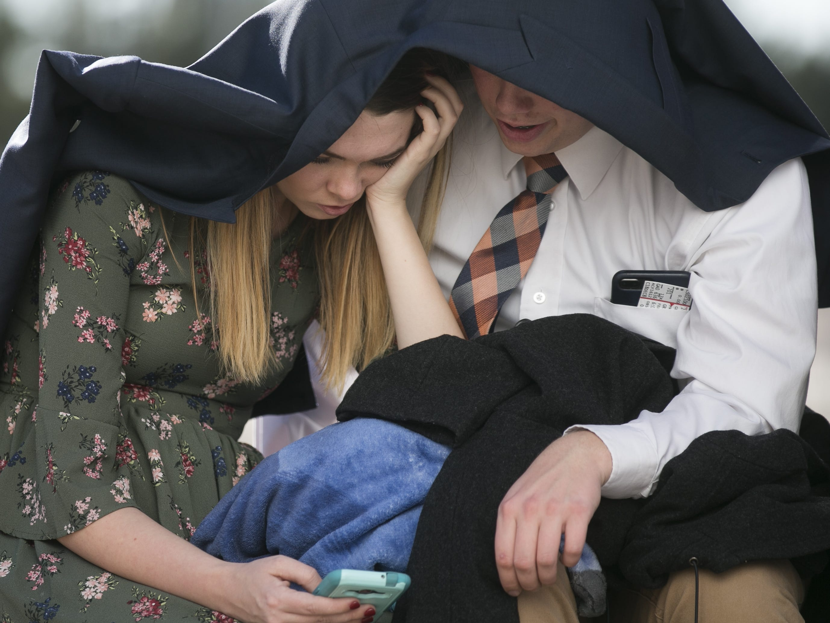Hannah Lunt (left) and Jacob Boyd (right) use Boyd's coat for shade as they wait with other members of the Church of Jesus Christ of Latter-day Saints at State Farm Stadium to hear church President Russell Nelson speak for a devotional in Glendale, Arizona on Sunday, Feb. 10, 2019.