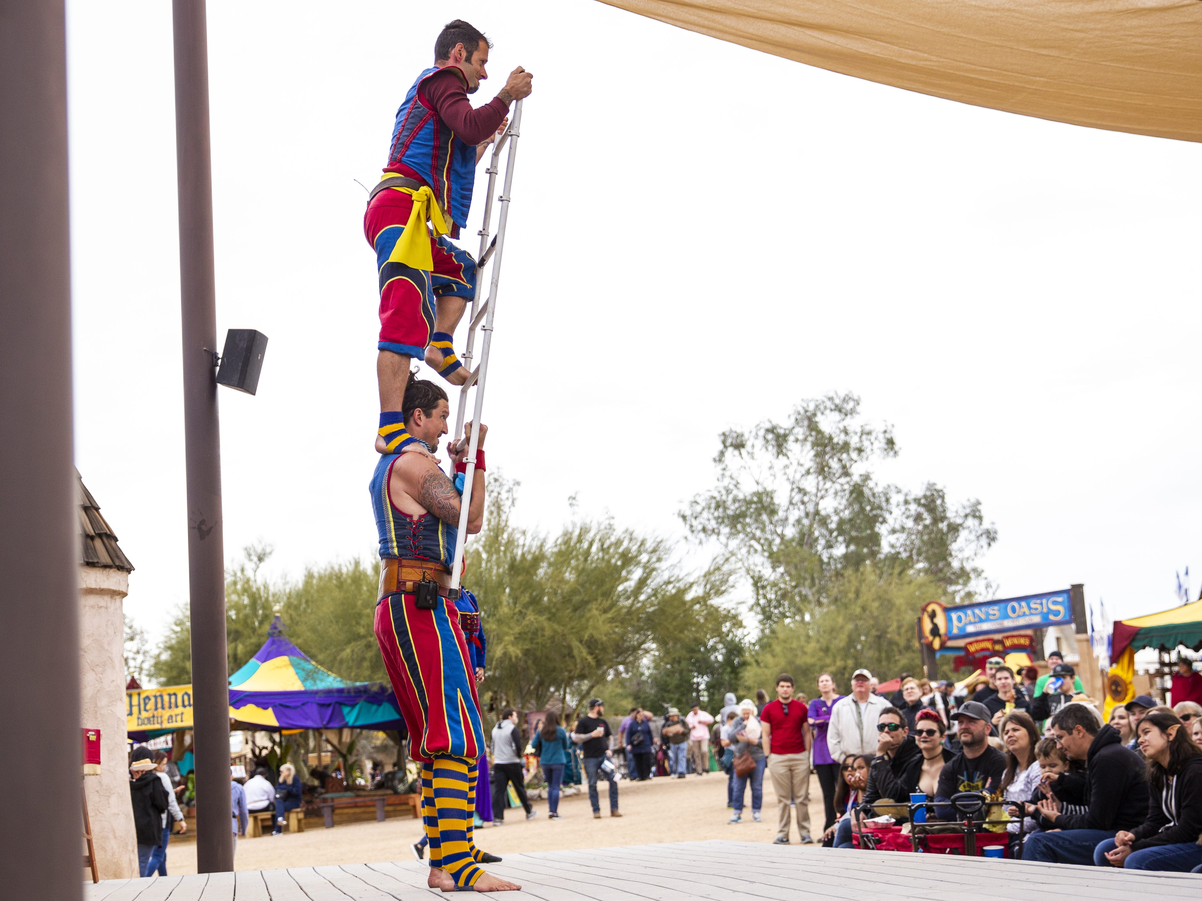 Cameron Tomele climbs a ladder held by James Freer at the Arizona Renaissance Festival 2019 on Feb. 9, 2019 in Gold Canyon, Ariz. Tomele and Freer are members of the comedy circus group Barely Balanced.