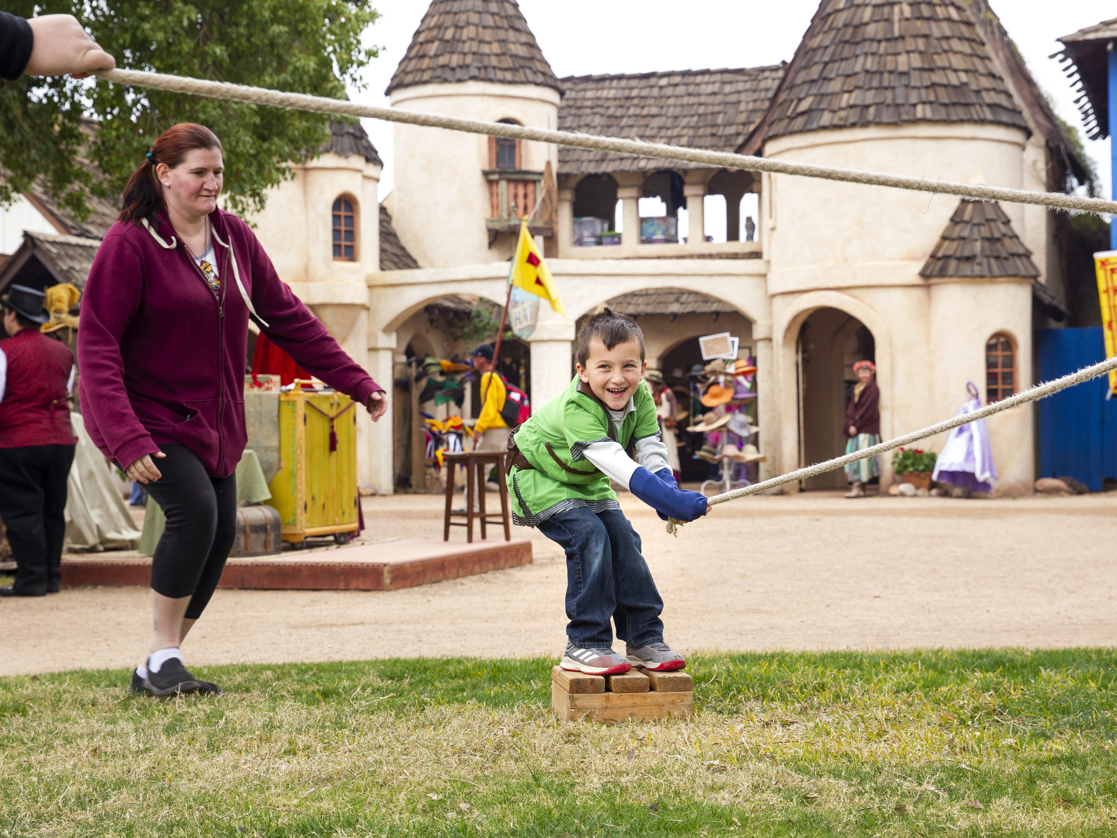 Andy Weeks, in green, competes against his family in a game of tug-of-war as Heather Vanderwall comes up from behind to help him at the Arizona Renaissance Festival 2019 on Feb. 9, 2019 in Gold Canyon, Ariz.