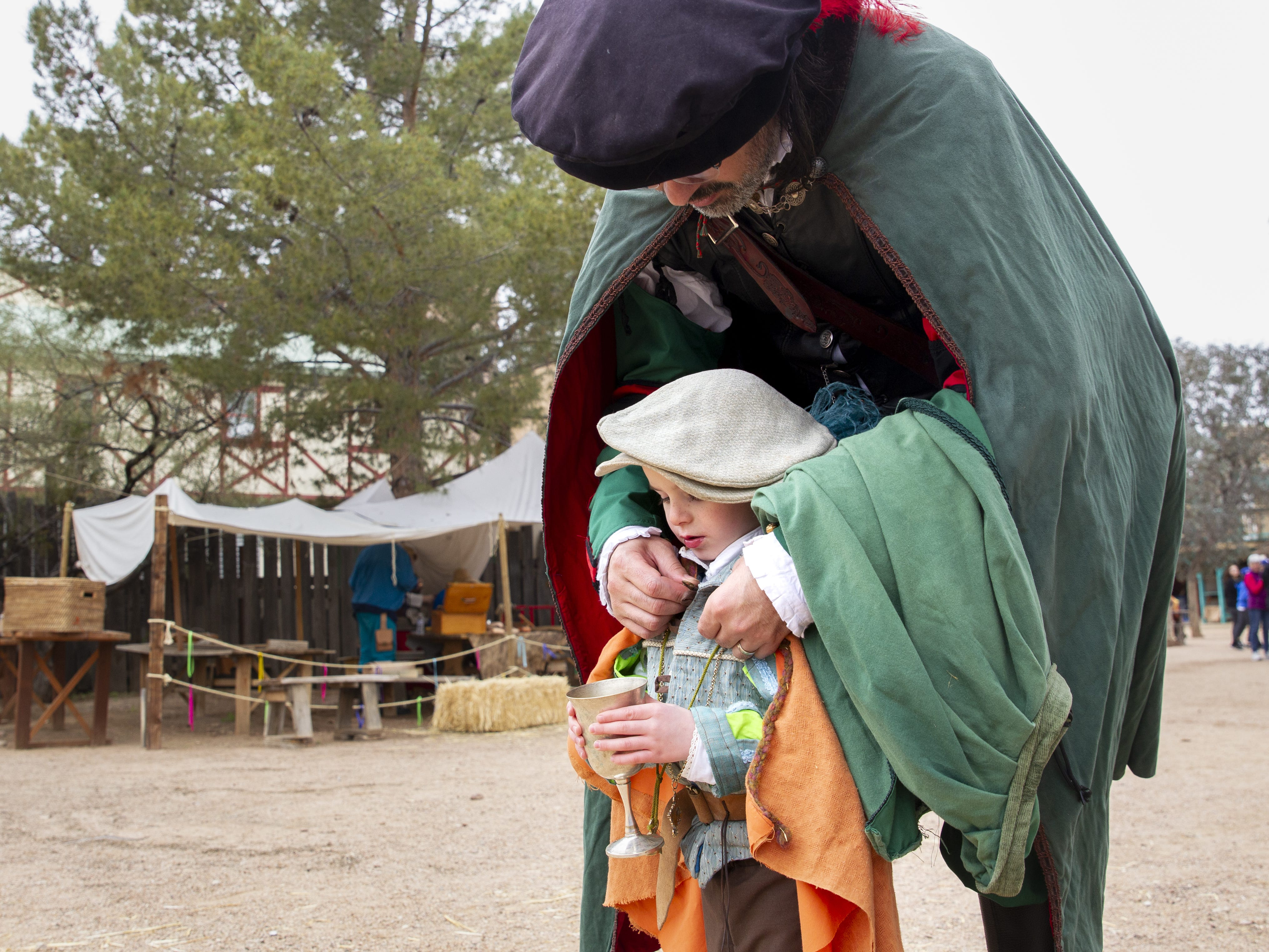 A man attending as the Sellsword puts a cloak on his son Romeo at the Arizona Renaissance Festival 2019 on Feb. 9, 2019 in Gold Canyon, Ariz.