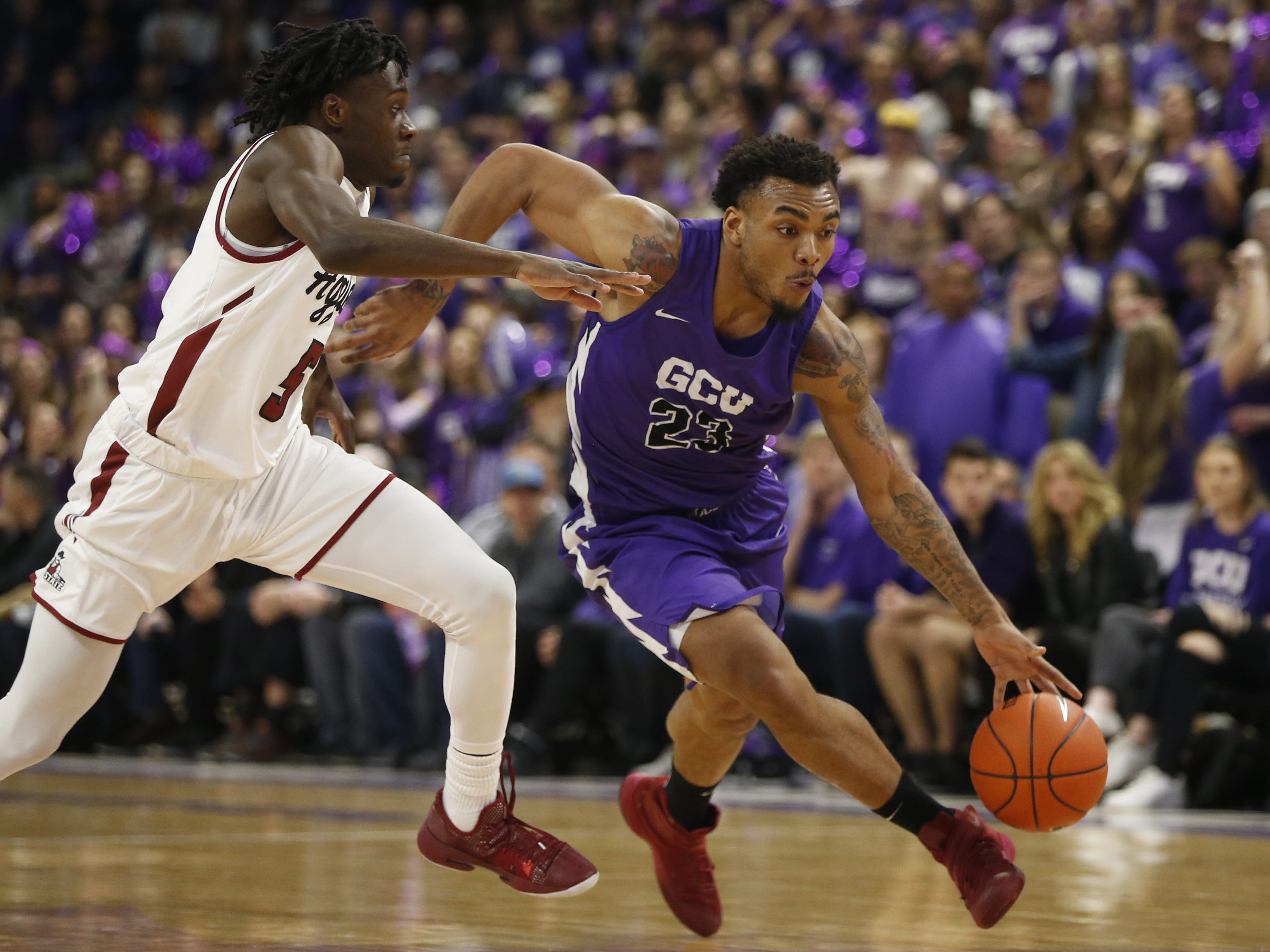 GCU's Carlos Johnson (23) drives against New Mexico State's Clayton Henry (5) during the first half at Grand Canyon University Arena in Phoenix, Ariz. on February 9, 2019.