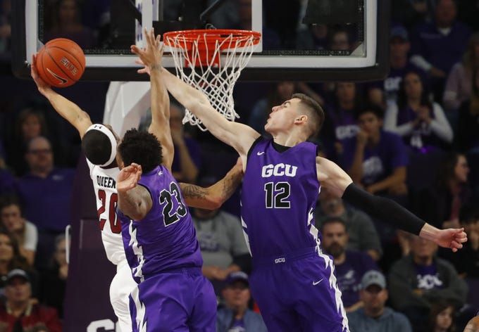 GCU's Roberts Blumbergs (12) and Carlos Johnson (23) attempt to block a layup from New Mexico State's Trevelin Queen (20) during the first half at Grand Canyon University Arena in Phoenix, Ariz. on February 9, 2019.