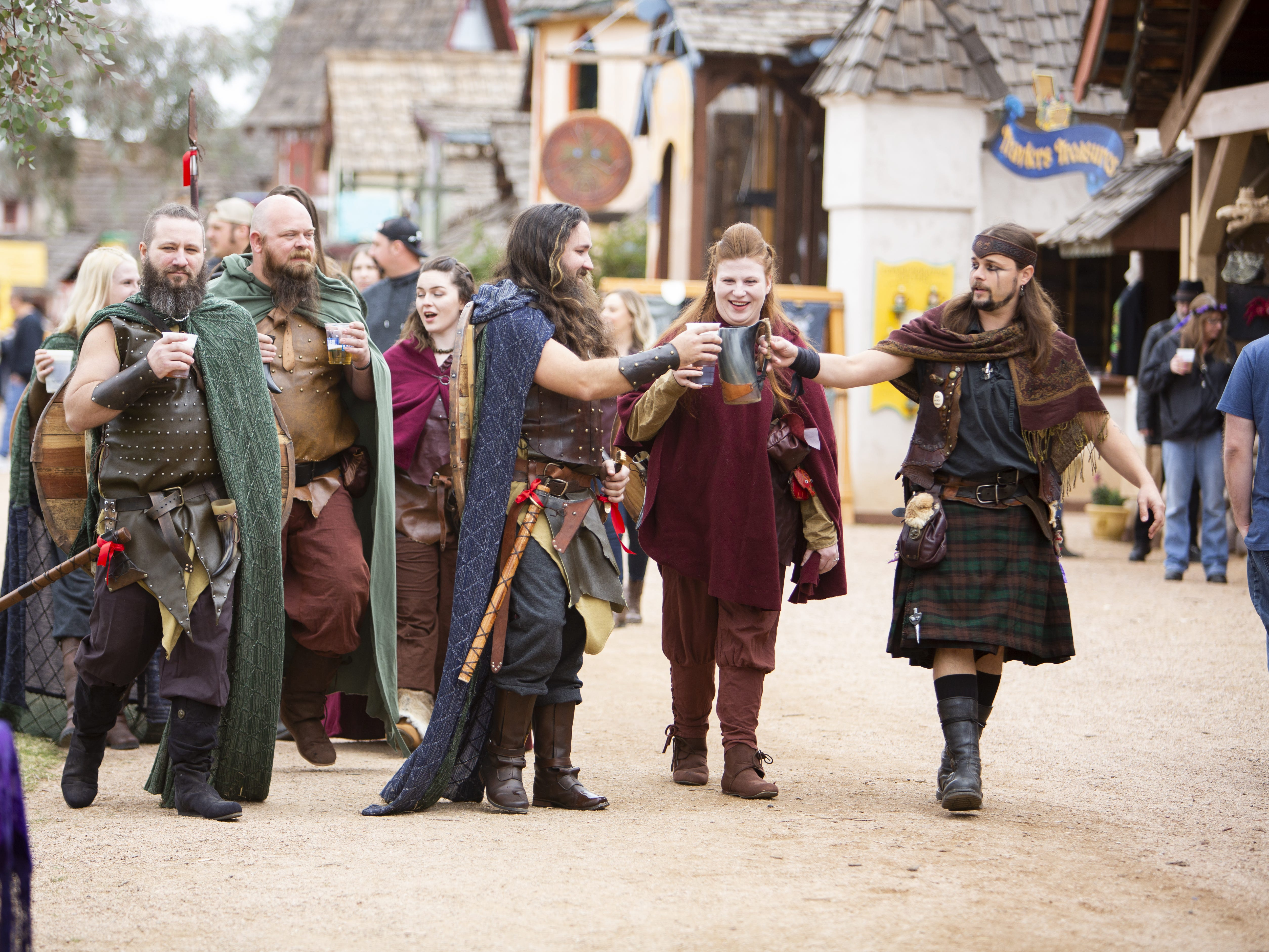 A group drinking beer in kilts and capes walks down a pathway at the Arizona Renaissance Festival 2019 on Feb. 9, 2019 in Gold Canyon, Ariz.