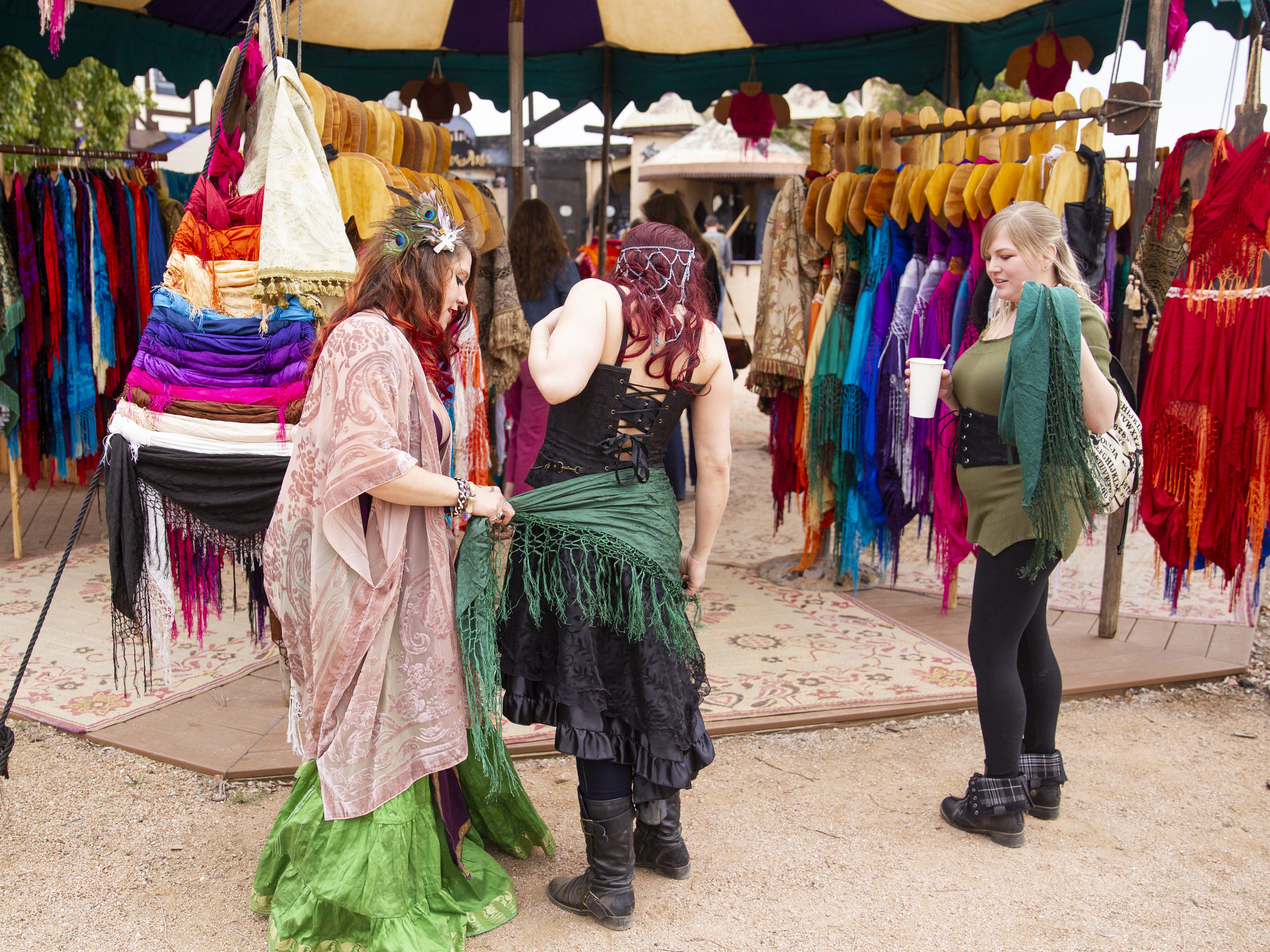 Jessica Cowan, left, and Kaila Harris, right, help Krystina Nation try on a shawl at the Arizona Renaissance Festival 2019 on Feb. 9, 2019 in Gold Canyon, Ariz.