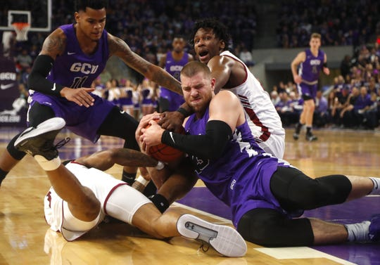 GCU's Michael Finke (42) fights for a loose ball with New Mexico State's C.J. Bobbitt (13) during the first half at Grand Canyon University Arena in Phoenix, Ariz. on February 9, 2019.