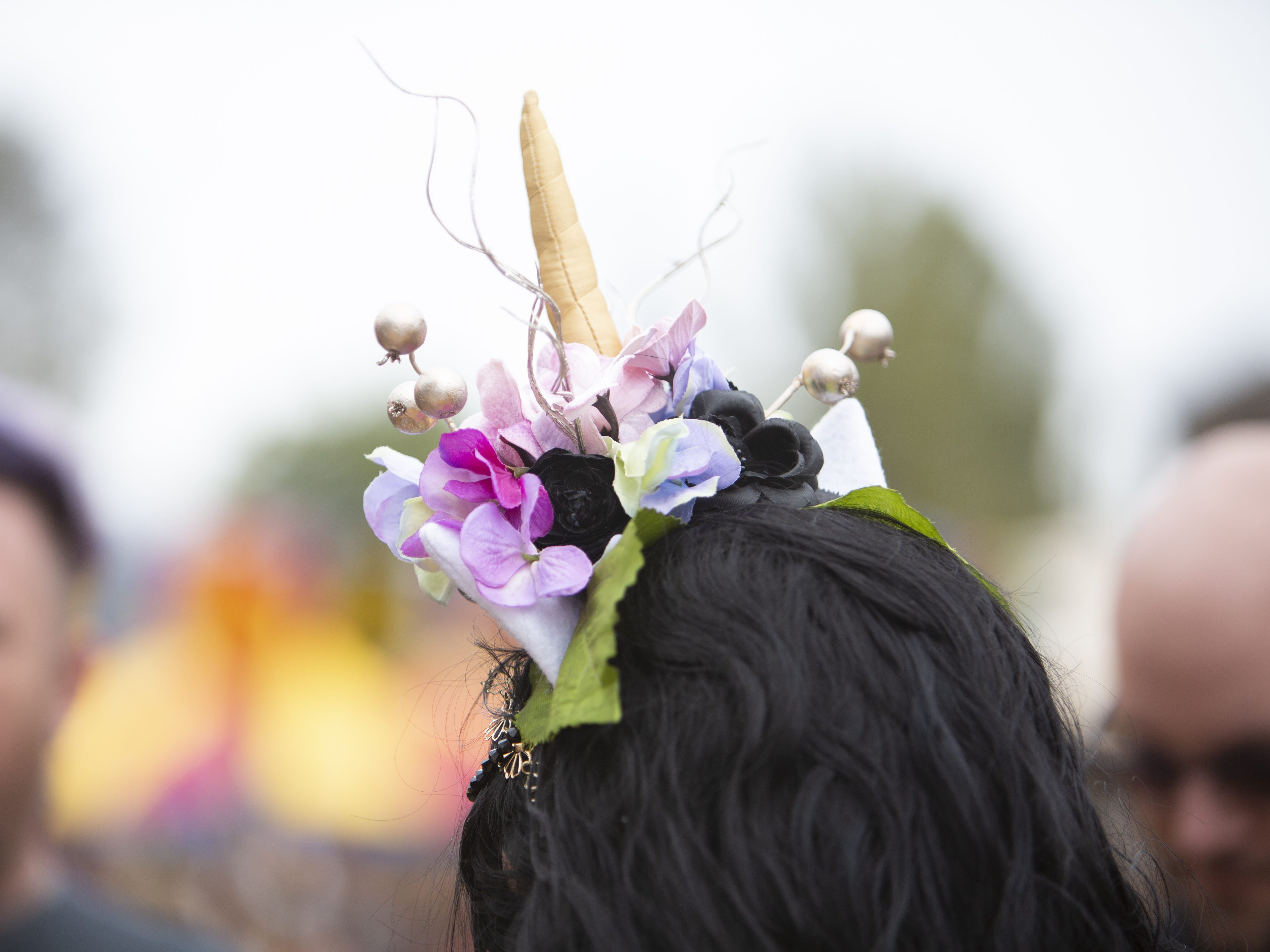 A woman pins a unicorn decoration in her hair at the Arizona Renaissance Festival 2019 on Feb. 9, 2019 in Gold Canyon, Ariz.