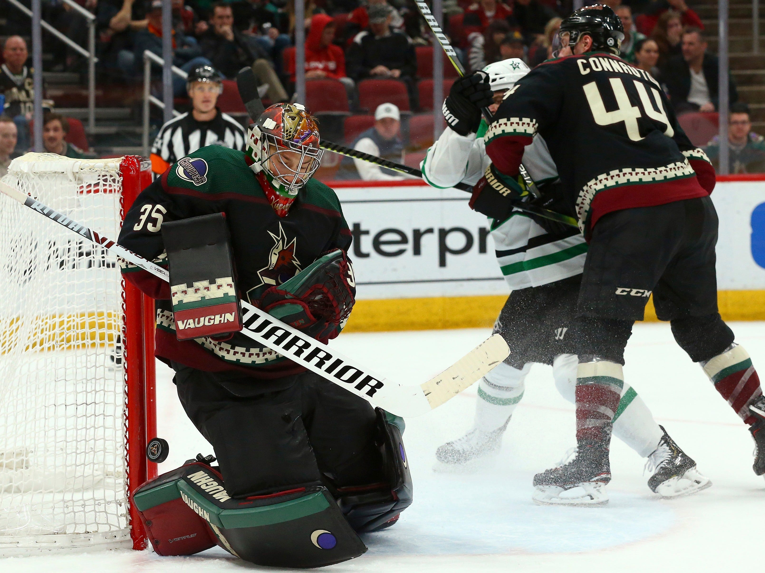 Arizona Coyotes goaltender Darcy Kuemper (35) makes a save as Coyotes defenseman Kevin Connauton (44) shoves Dallas Stars left wing Blake Comeau, second from right, during the third period of an NHL hockey game Saturday, Feb. 9, 2019, in Glendale, Ariz. (AP Photo/Ross D. Franklin)
