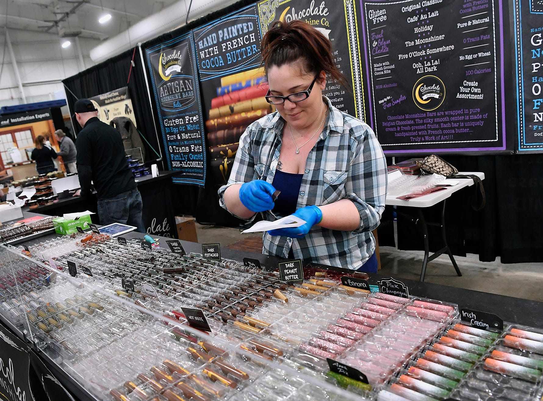 Kayla Nieder gathers chocolates for a customer at the Chocolate Moonshine Company booth at the York Builders Association Home & Garden Show in the Utz Arena, Sunday, February 10, 2019.John A. Pavoncello photo