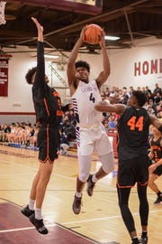 Former Irondequoit star Gerald Drumgoole, who transferred to the La Lumiere School in La Porte, Indiana, splits two Wasatch Academy defenders.