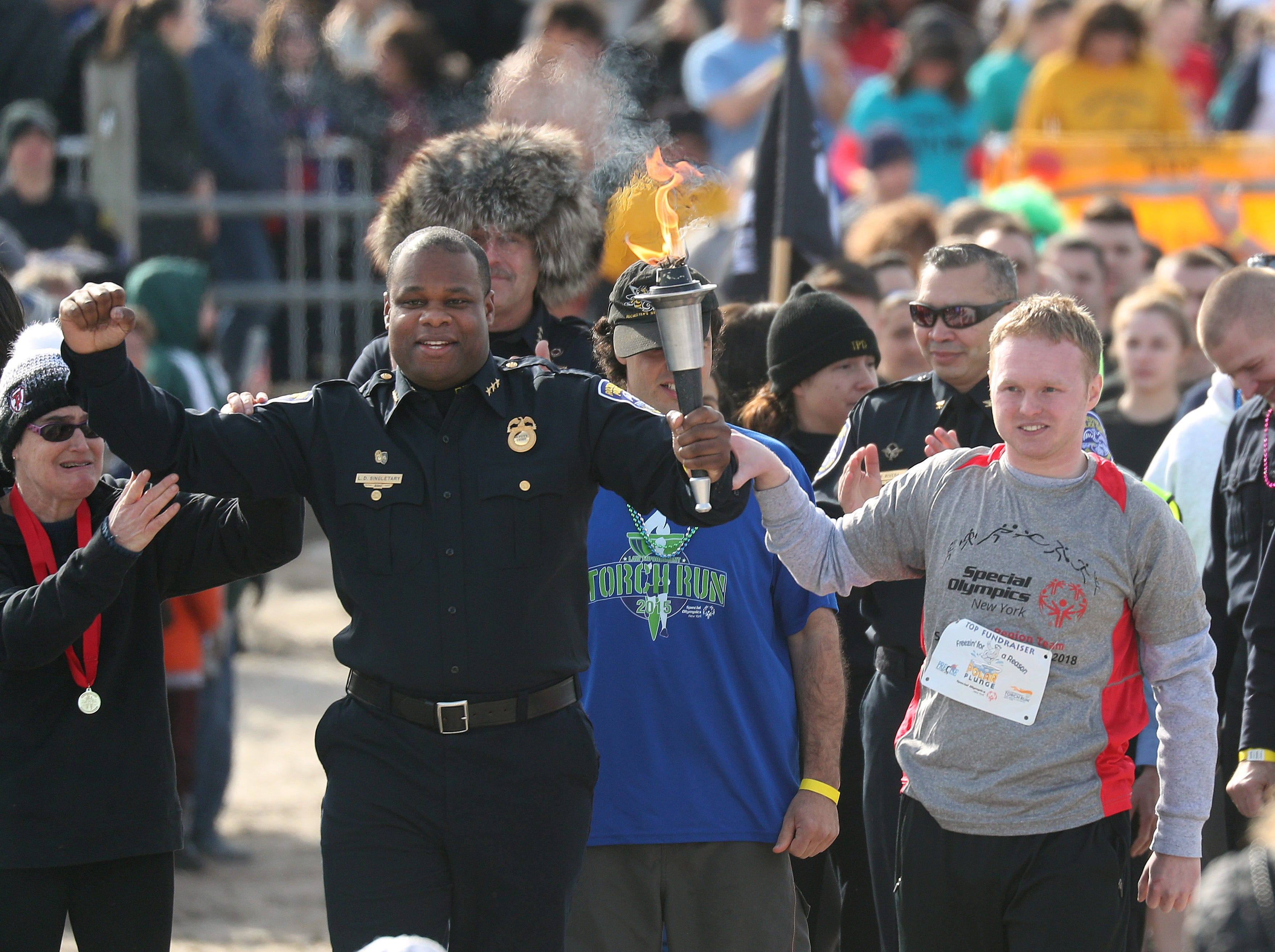 Rochester Police Deputy Chief LaRon Singletary carries the torch at the start of the annual Polar Plunge at Charlotte Beach.