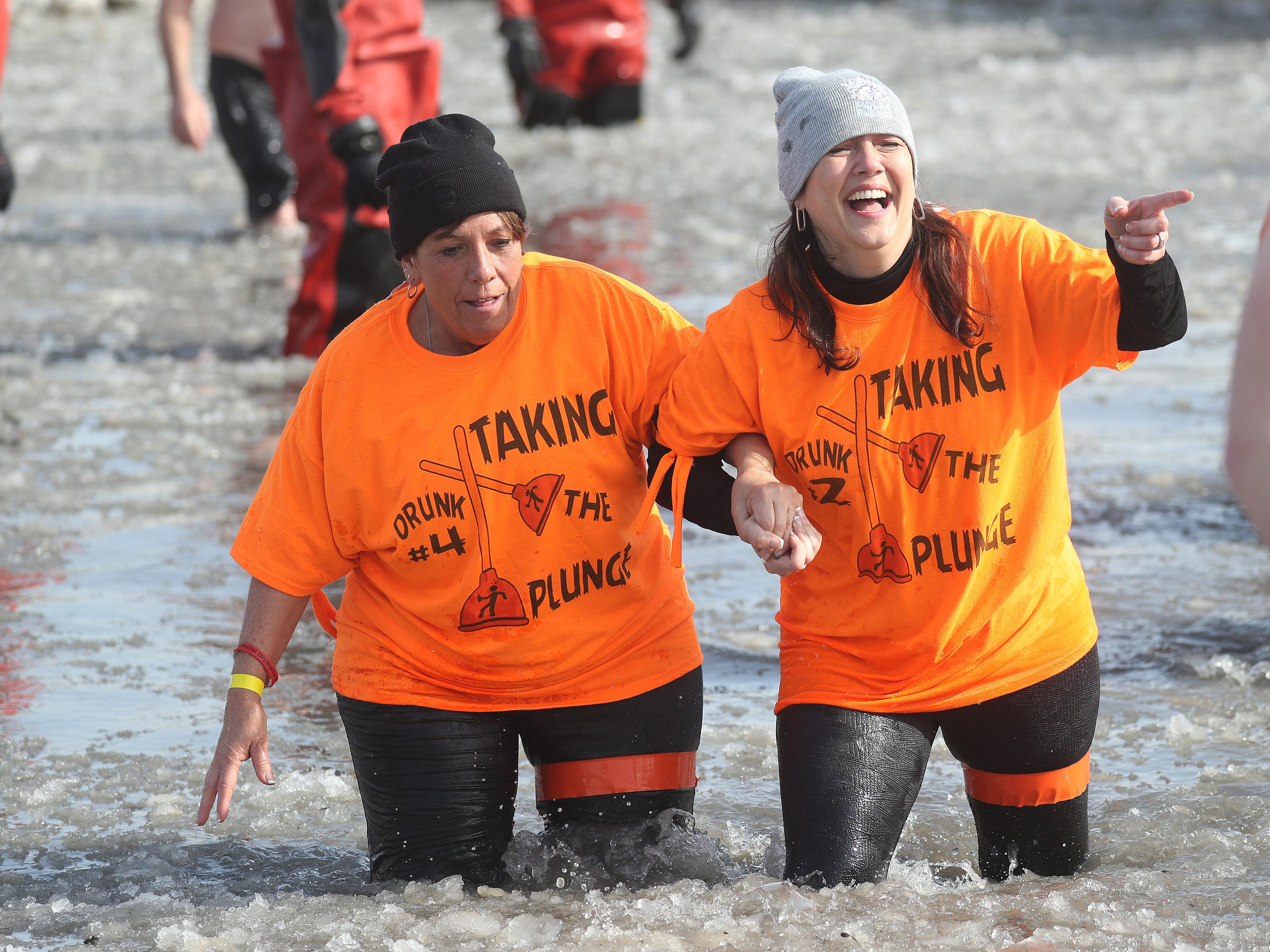 Marcia Catallo (left) and Provie Morris make their way out of the frigid waters of Lake Ontario as part of the annual Polar Plunge.