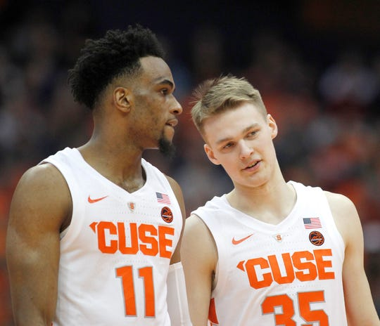 Syracuse's Oshae Brissett, left, and Buddy Boeheim, right, talk during a timeout during the second half of an NCAA college basketball game against Boston College in Syracuse, N.Y., Saturday, Feb. 9, 2019. Syracuse won 67-56.
