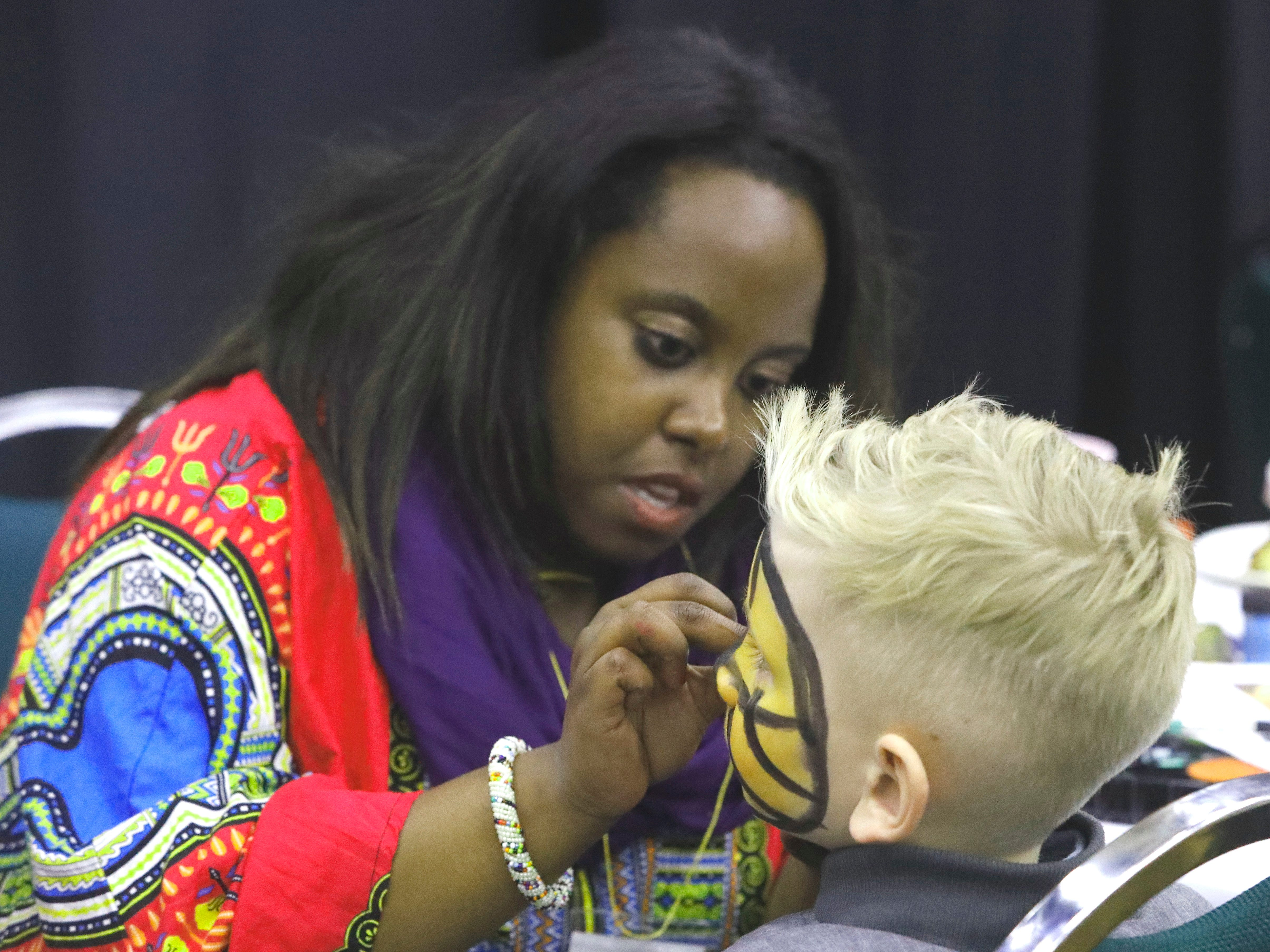 Njeri Mwaniki of the United States, whose family is from Kenya, does face-painting during the Festival of Cultures hosted by Bethel Church on Feb. 9, 2019.