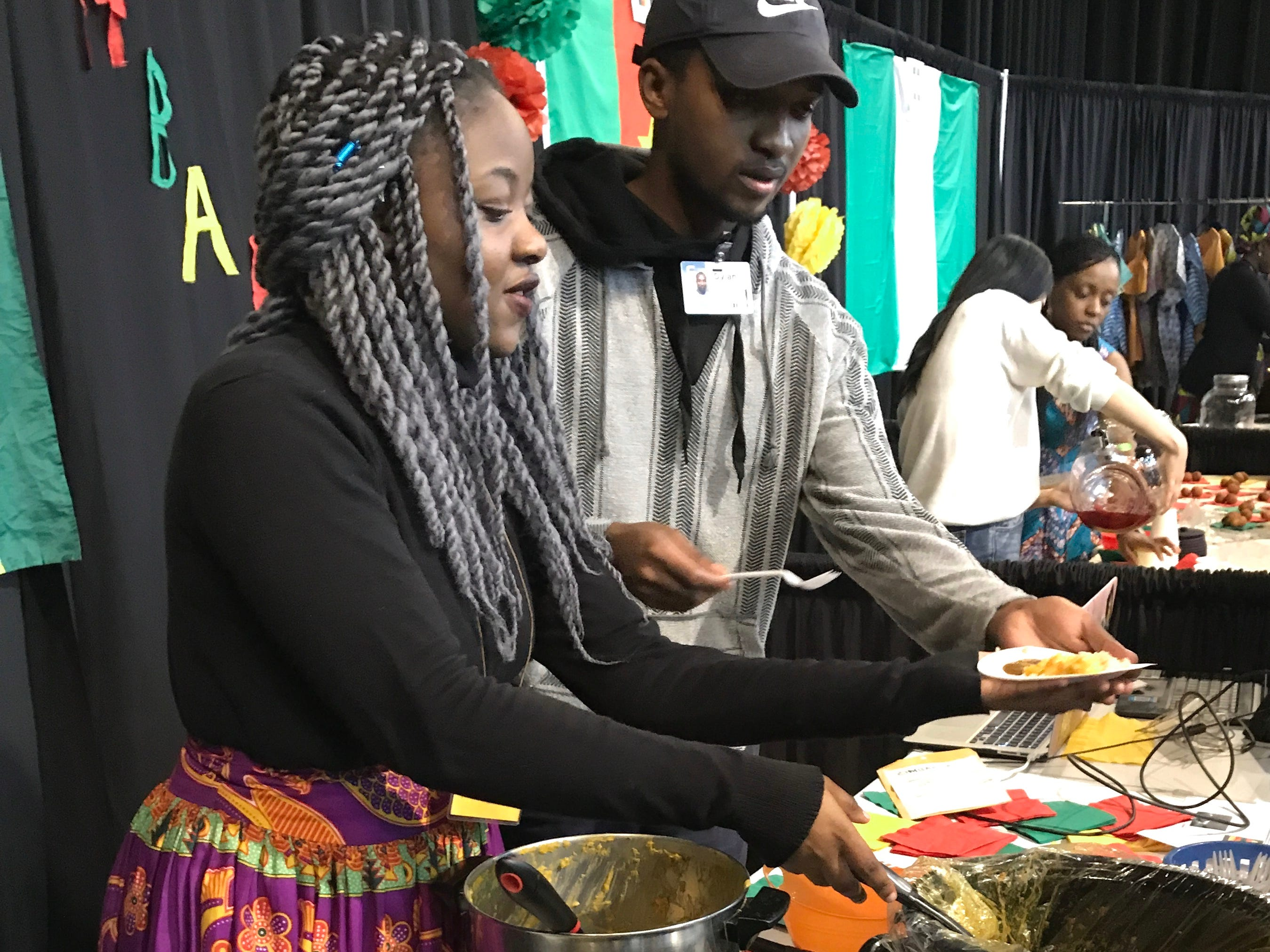 Ruzivo Chisaka, left, and Dylan Mafukidze serve food samples representing Zimbabwe during the annual Festival of Cultures hosted by Bethel Church in the Redding Civic Auditorium on Feb. 9, 2019. Bethel School of Supernatural Ministry students from more than 50 countries participated.