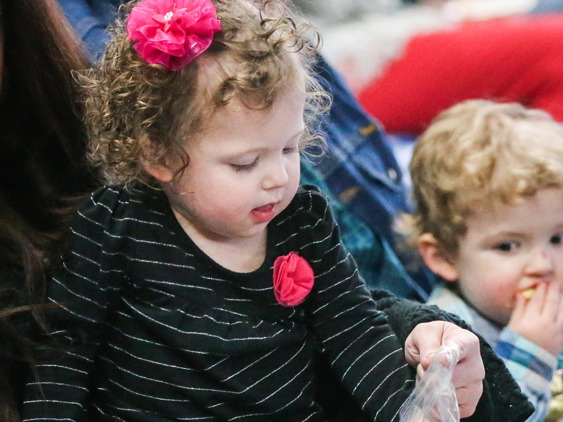 Kensleigh Phillips, 2, center, digs into the popcorn before the San Angelo Stock Show & Rodeo show Saturday, Feb. 9, 2019, at Foster Communications Coliseum.
