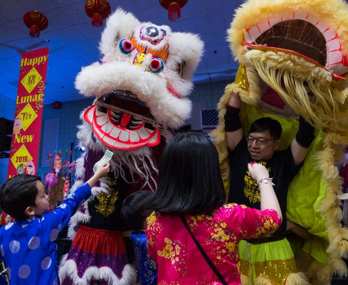 Kids give money to the lion performers during the Lion Dance at the Lunar New Year Festival in Sioux Falls, S.D., Saturday, Feb. 9, 2019.