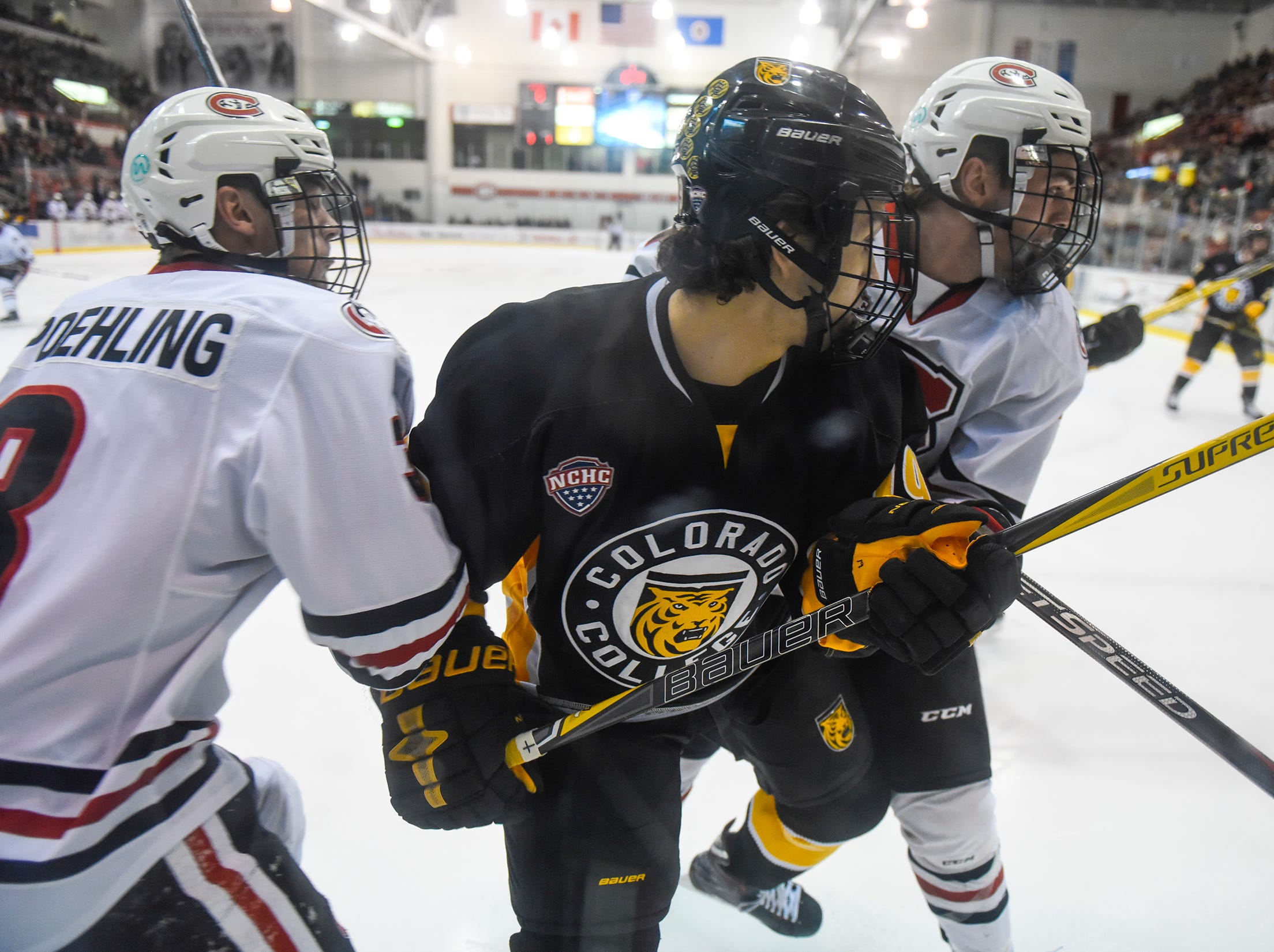 Troy Conzo of Colorado College is sandwiched between Jack Poehling and Nick Poehling 19, 3-7 during the first period of the Saturday, Feb. 9, game at the Herb Brooks National Hockey Center in St. Cloud.