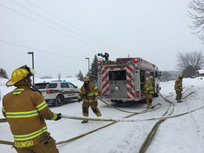 Sauk Rapids Fire Department hauls out hoses under a fresh blanket of snow Sunday morning after extinguishing an apartment fire.
