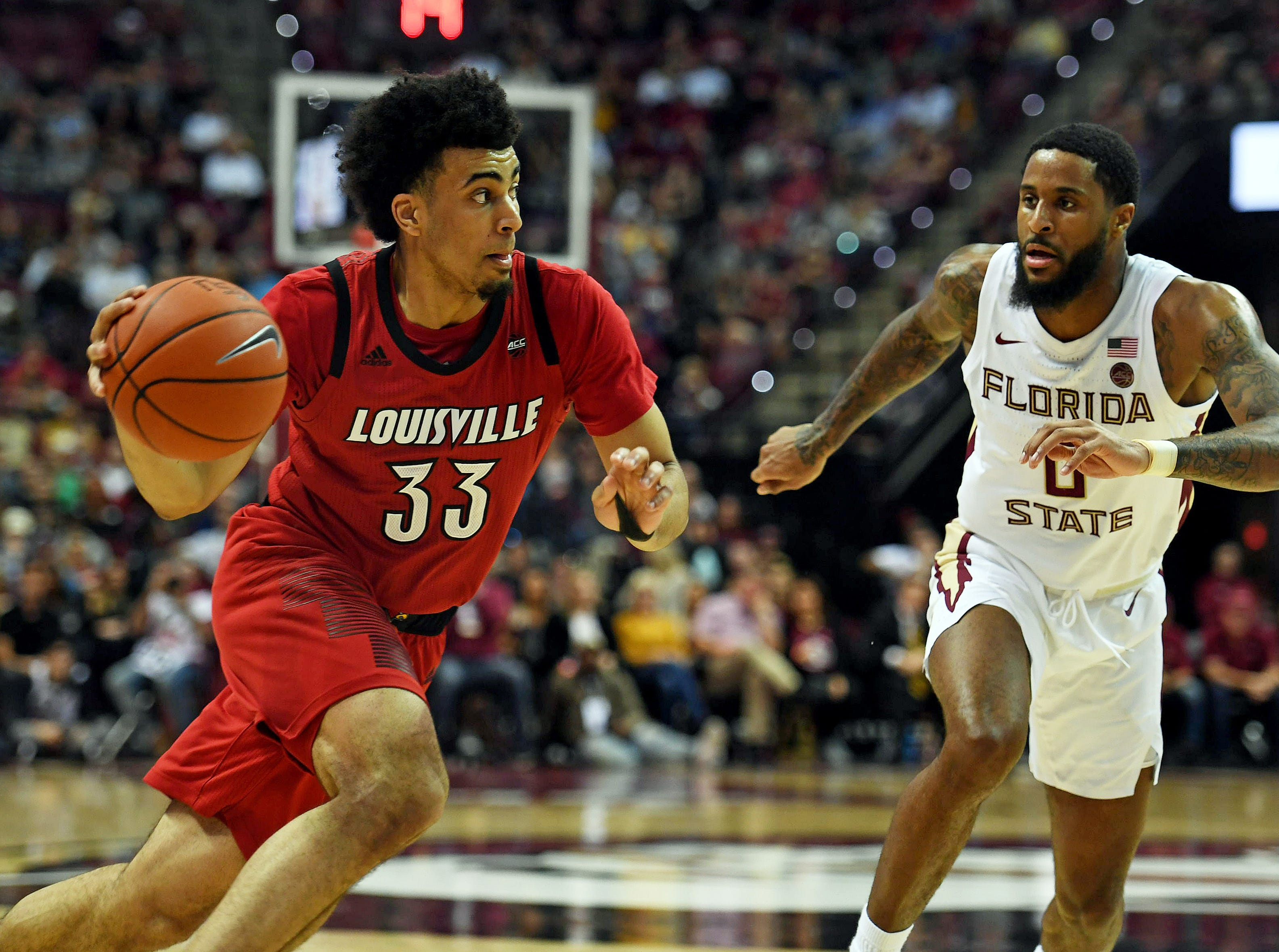 Feb 9, 2019; Tallahassee, FL, USA; Louisville Cardinals forward Jordan Nwora (33) drives the ball against Florida State Seminoles forward Phil Cofer (0) during the second half at Donald L. Tucker Center. Mandatory Credit: Melina Myers-USA TODAY Sports