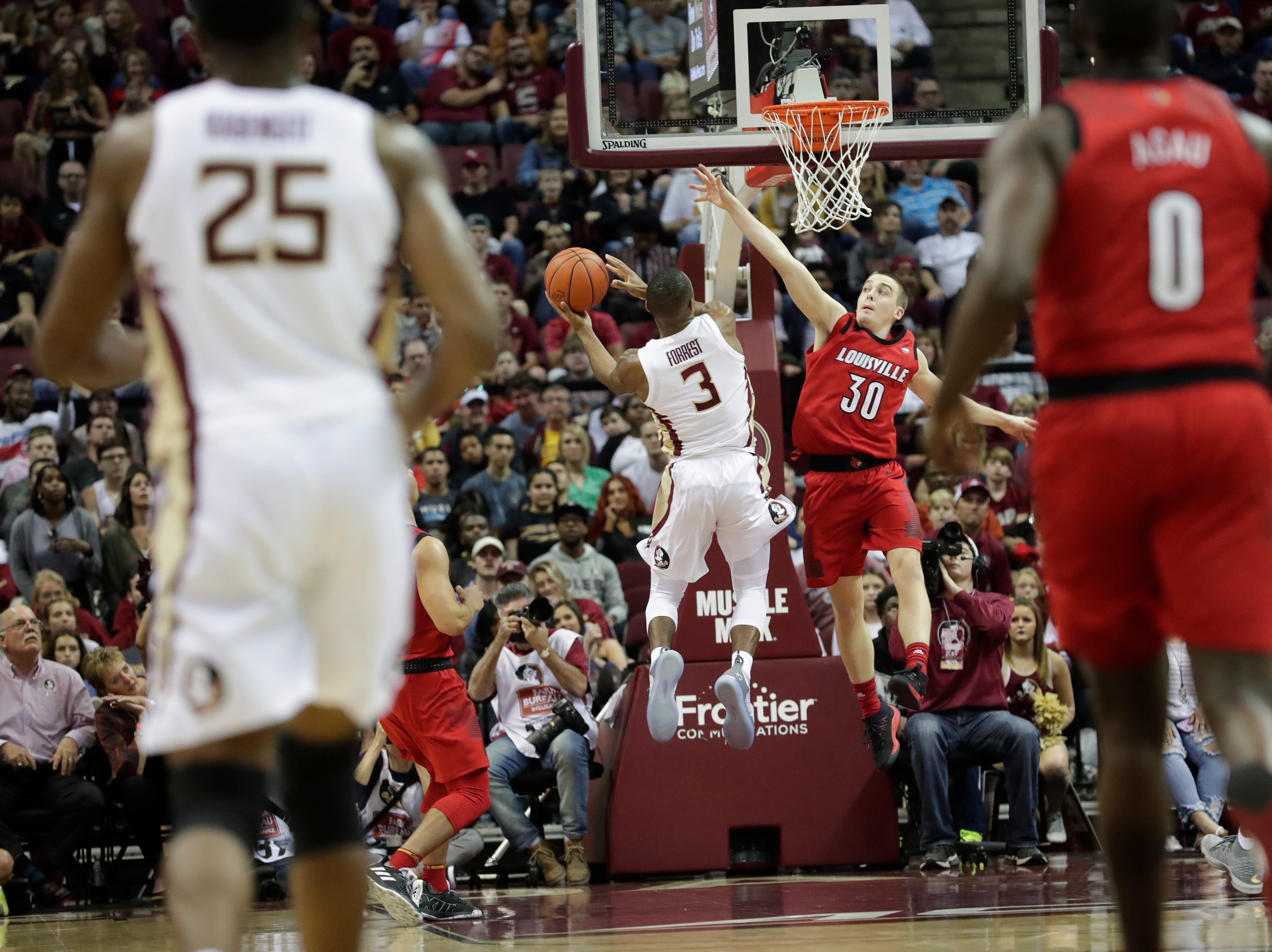 Florida State Seminoles guard Trent Forrest (3) drives in a layup with Louisville Cardinals guard Ryan McMahon (30) going up to block the shot. The Florida State Seminoles host the Louisville Cardinals at the Tucker Civic Center, Saturday Feb. 9, 2019.