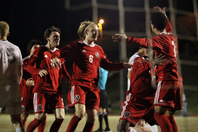 Leon's Sy Fontenot (1) is mobbed after scoring the game-winning goal as the Lions' boys soccer team beat Niceville 1-0 in a Region 1-4A semifinal on Feb. 9, 2019.