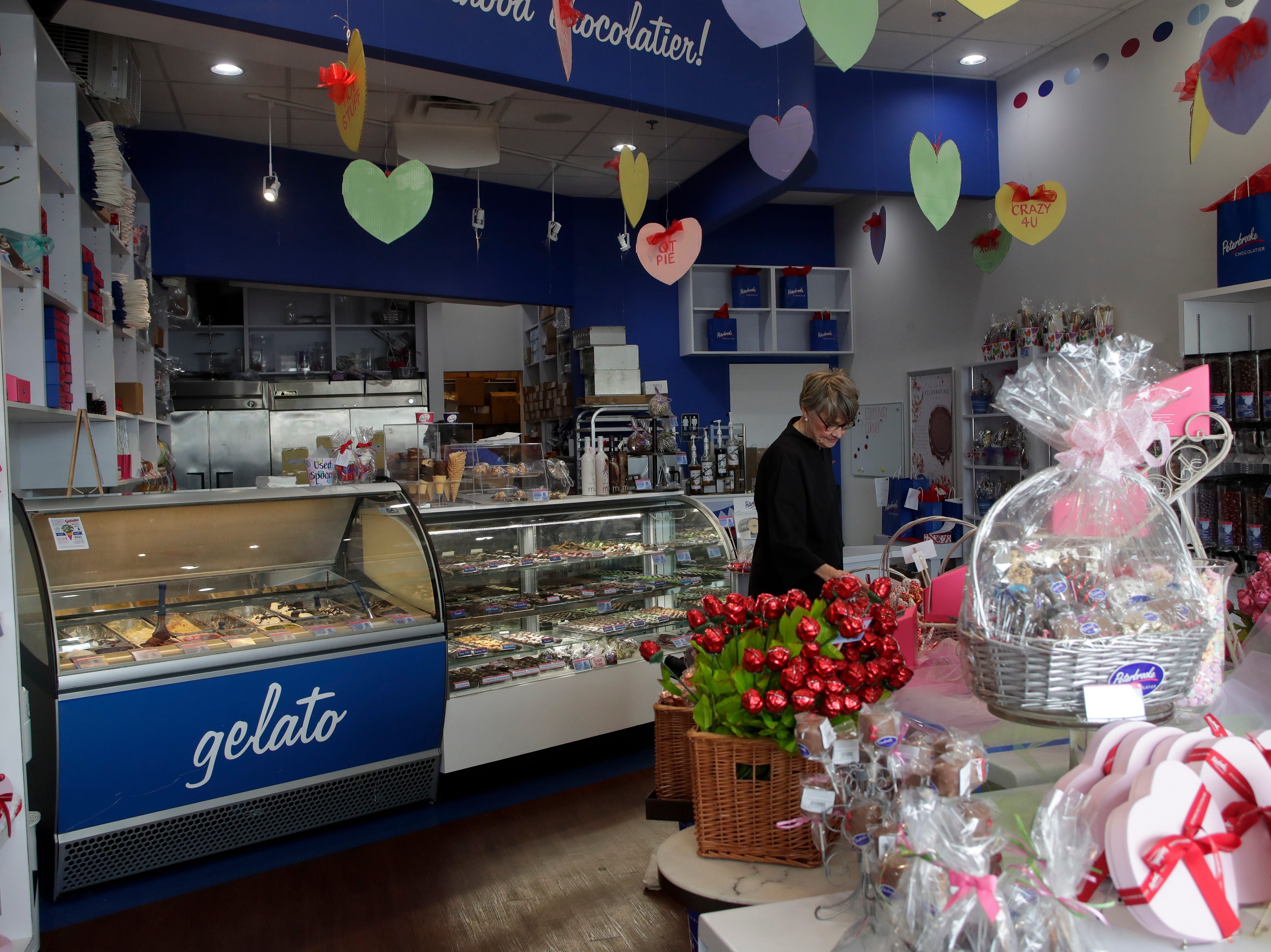 Dot Herbert, manager of Peterbrooke Chocolatier, adjusts a display Sunday, Feb. 10, 2019, as she prepares the store for their busiest single day of business, Valentine's Day.