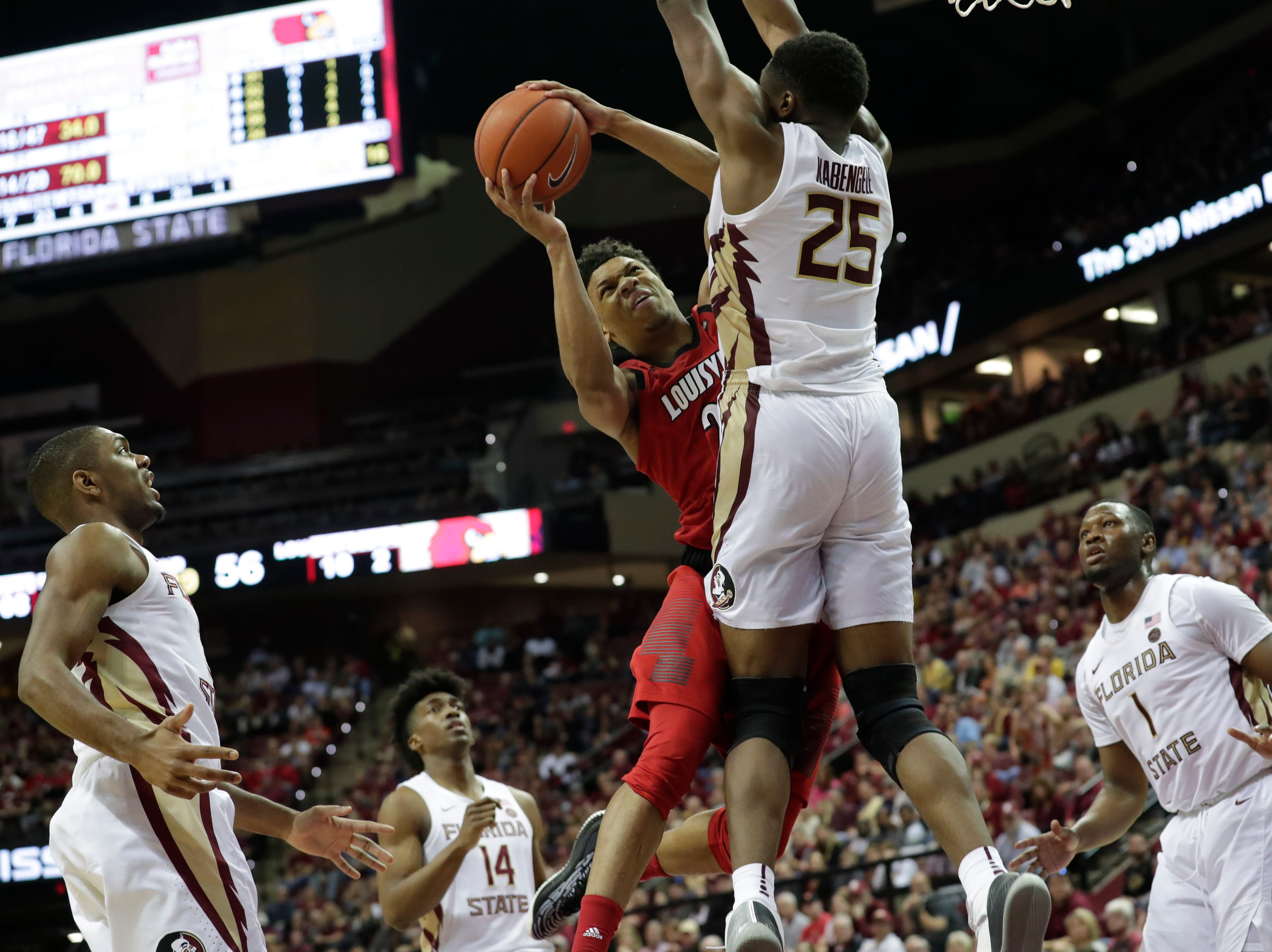 Louisville Cardinals center Steven Enoch (23) drives the ball to the hoop and tries shoot over Florida State Seminoles forward Mfiondu Kabengele (25). The Florida State Seminoles host the Louisville Cardinals at the Tucker Civic Center, Saturday Feb. 9, 2019.