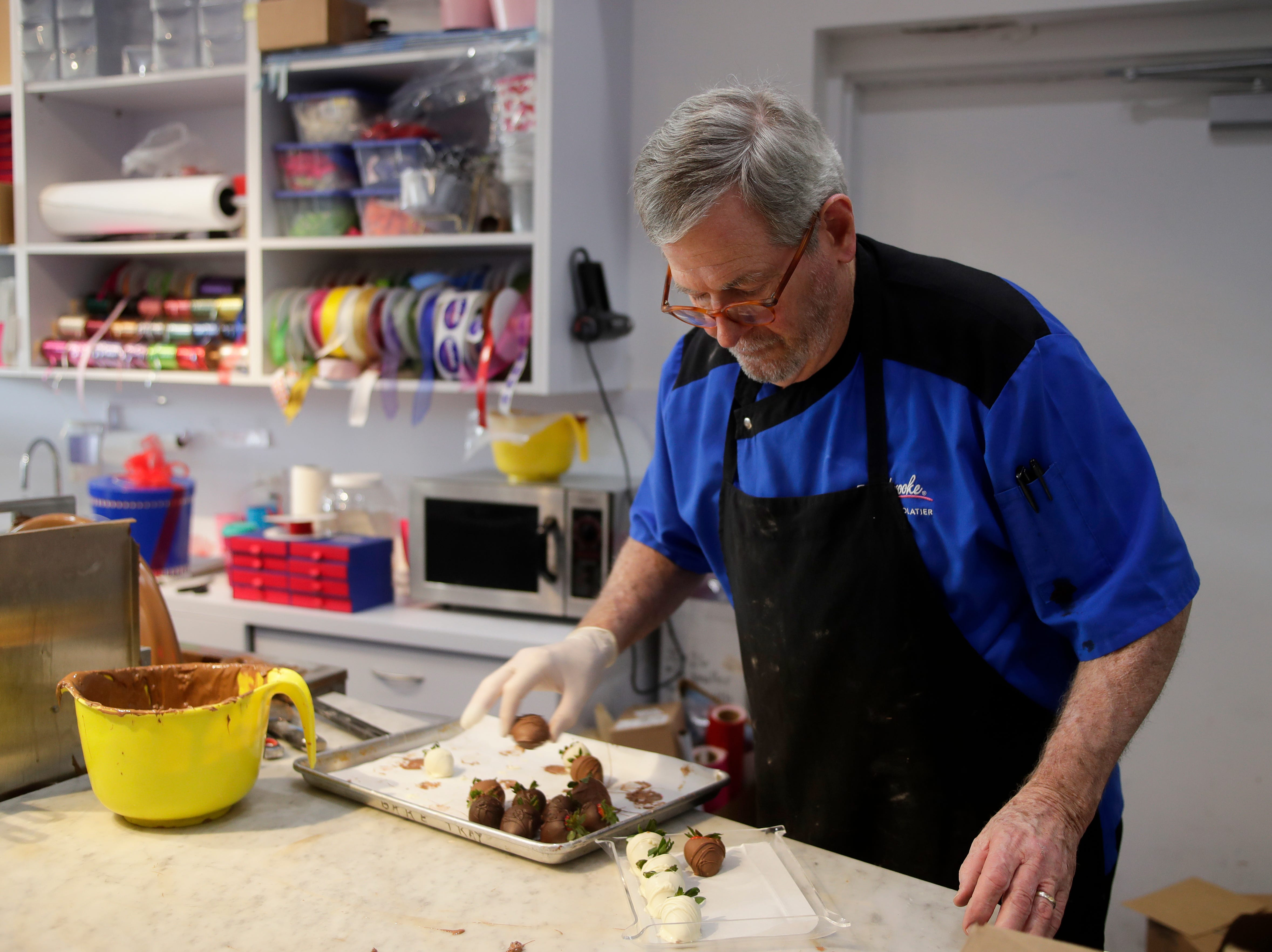Richard Herbert, manager of Peterbrooke Chocoaltier, prepares chocolate covered strawberries to be sold at the store Sunday, Feb. 10, 2019. The Tallahassee Peterbrooke location will sell between 3,500 and 4,000 chocolate covered strawberries on Valentine's Day.