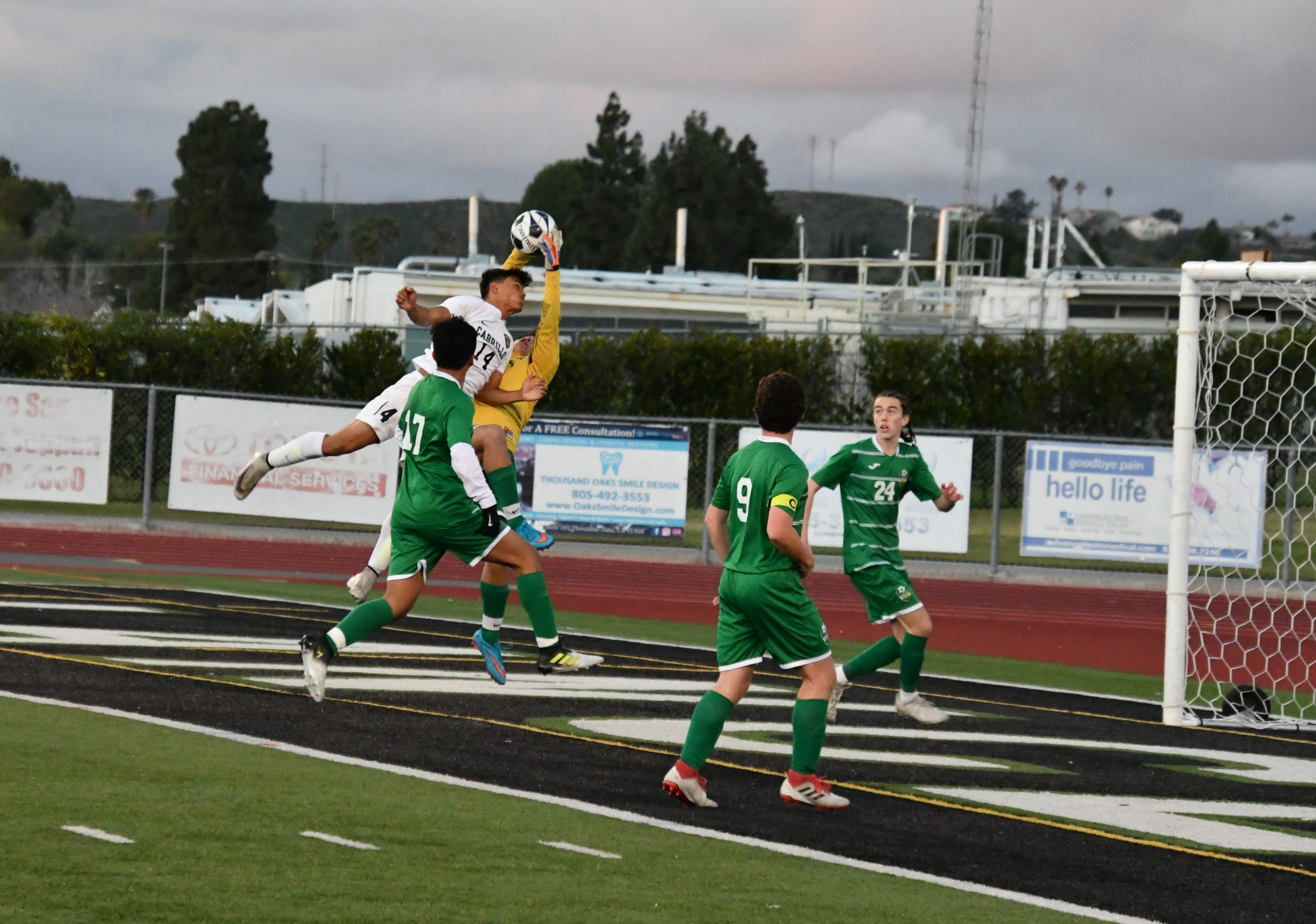 Thousand Oaks High goalkeeper Ramon Yerena rises to make a save under pressure on Saturday night in the second round of the CIF-Southern Section Division 2 playoffs in Thousand Oaks. Long Beach-Cabrillo won, 2-0.