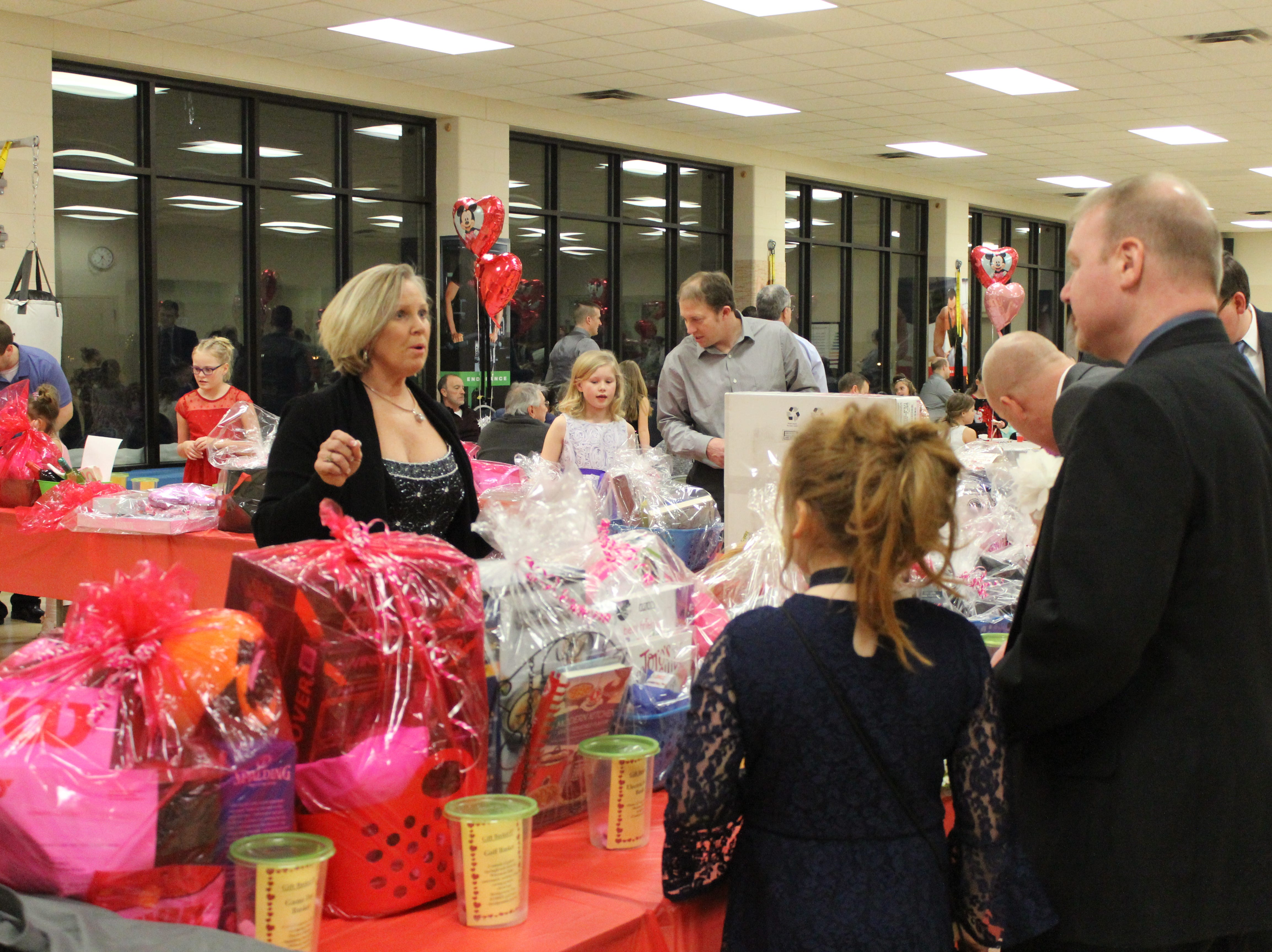 Fathers and daughters enjoy a night out at the annual Woodson YMCA Father Daughter dance, while looking over some of the baskets they could win in the raffle.