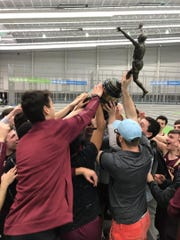 Iona Prep hoists trophy while celebrating winning the 2019 State Catholic indoor track championship.