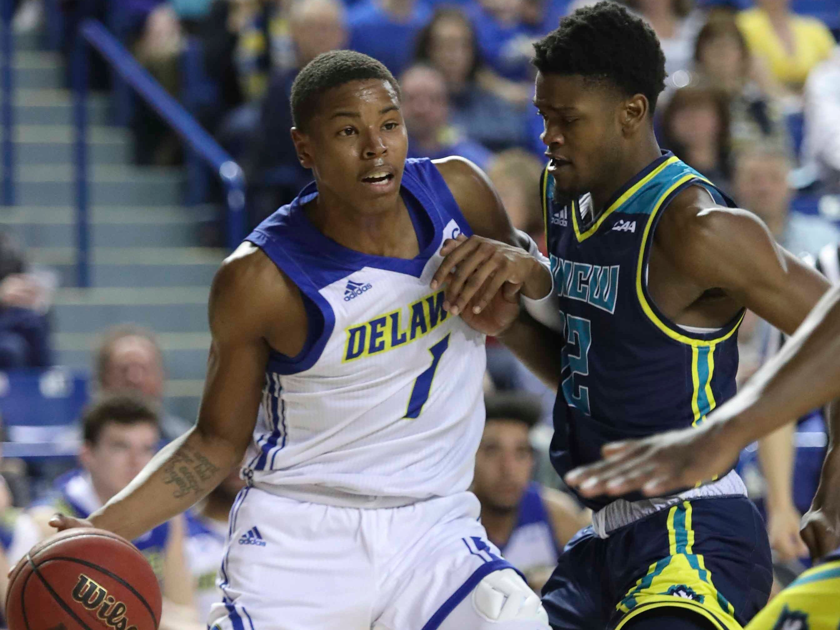 Delaware' Kevin Anderson (1) is fouled on a drive by UNC-Wilmington's Jay Estime' in the second half of Delaware's 70-66 win at the Bob Carpenter Center Saturday.