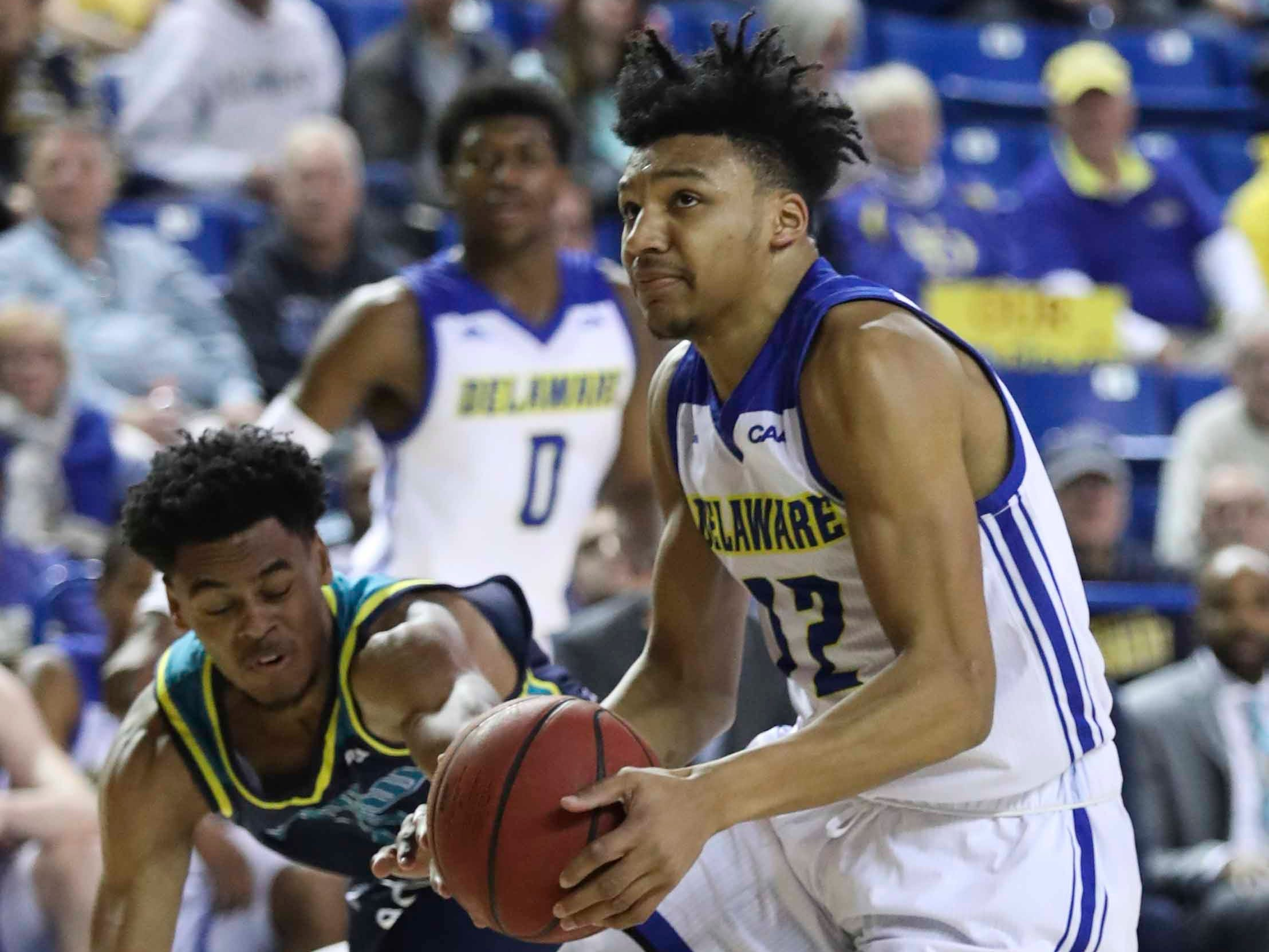 Delaware's Ithiel Horton (12) nearly loses the ball but instead ends up scoring ahead of UNC-Wilmington's Devontae Cacok in the second half of Delaware's 70-66 win at the Bob Carpenter Center Saturday.