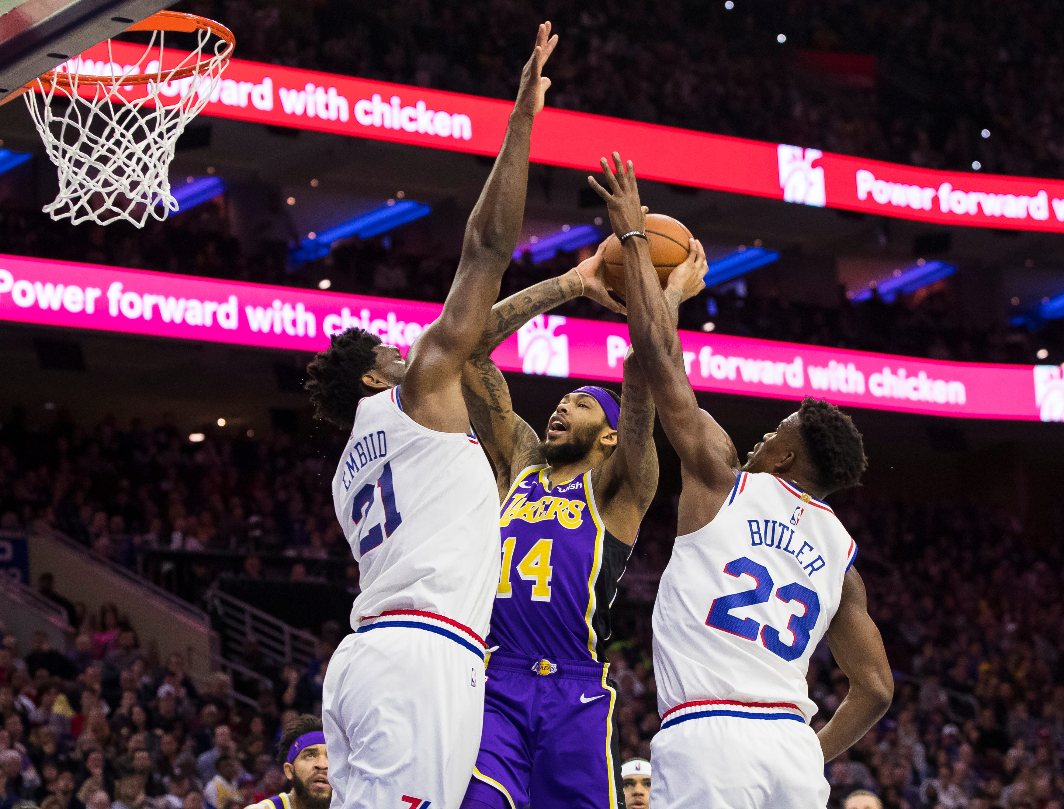 Los Angeles Lakers' Brandon Ingram, center, goes up for the shot against Philadelphia 76ers' Joel Embiid, left, of Cameroon, and Jimmy Butler, right, during the first half of an NBA basketball game, Sunday, Feb. 10, 2019, in Philadelphia. (AP Photo/Chris Szagola)