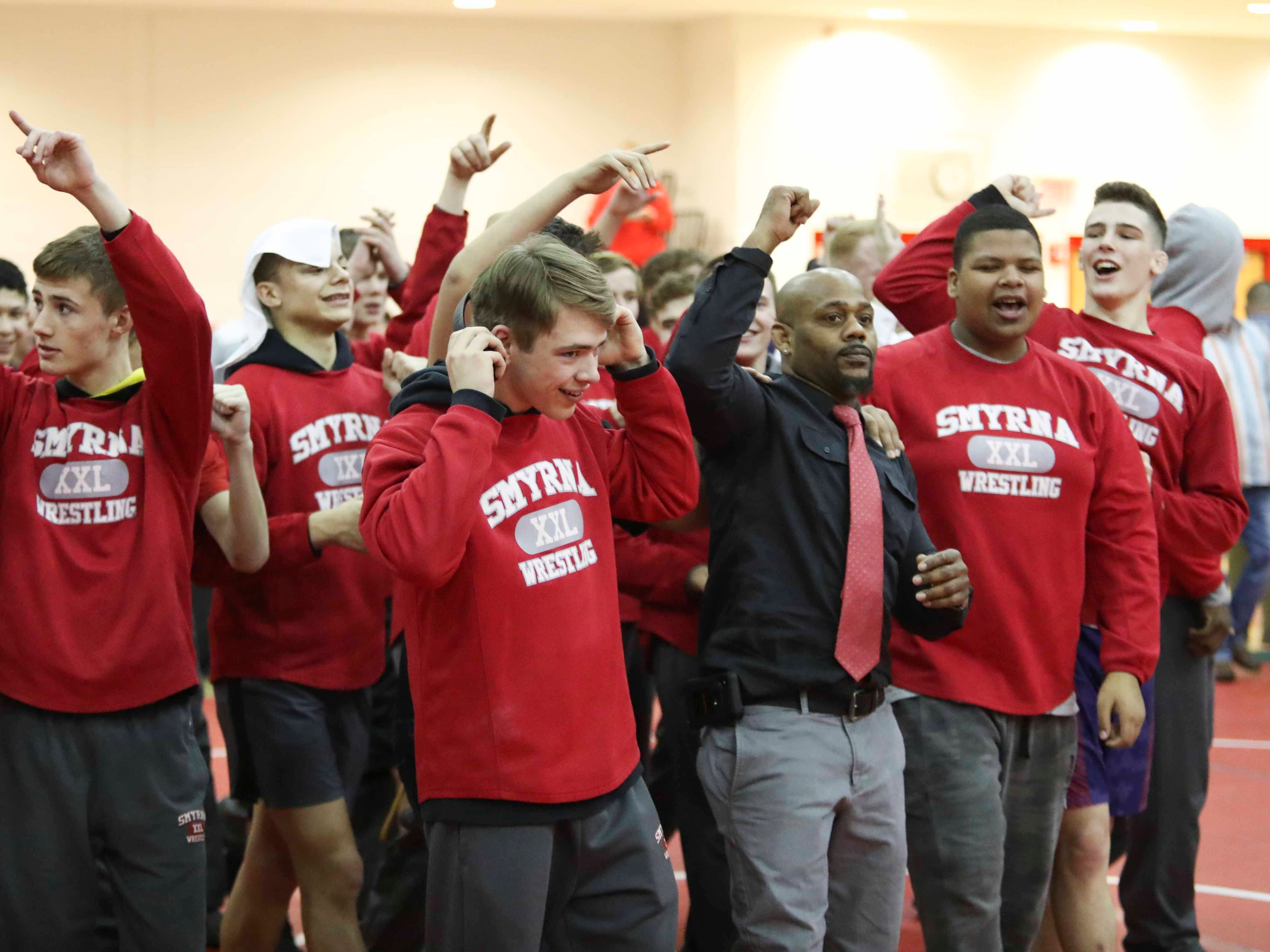 Smyrna, lead by coach Aaron Harris cheers after winning the DIAA Division I dual meet championship in the final round versus Caesar Rodney Saturday at Smyrna High School.