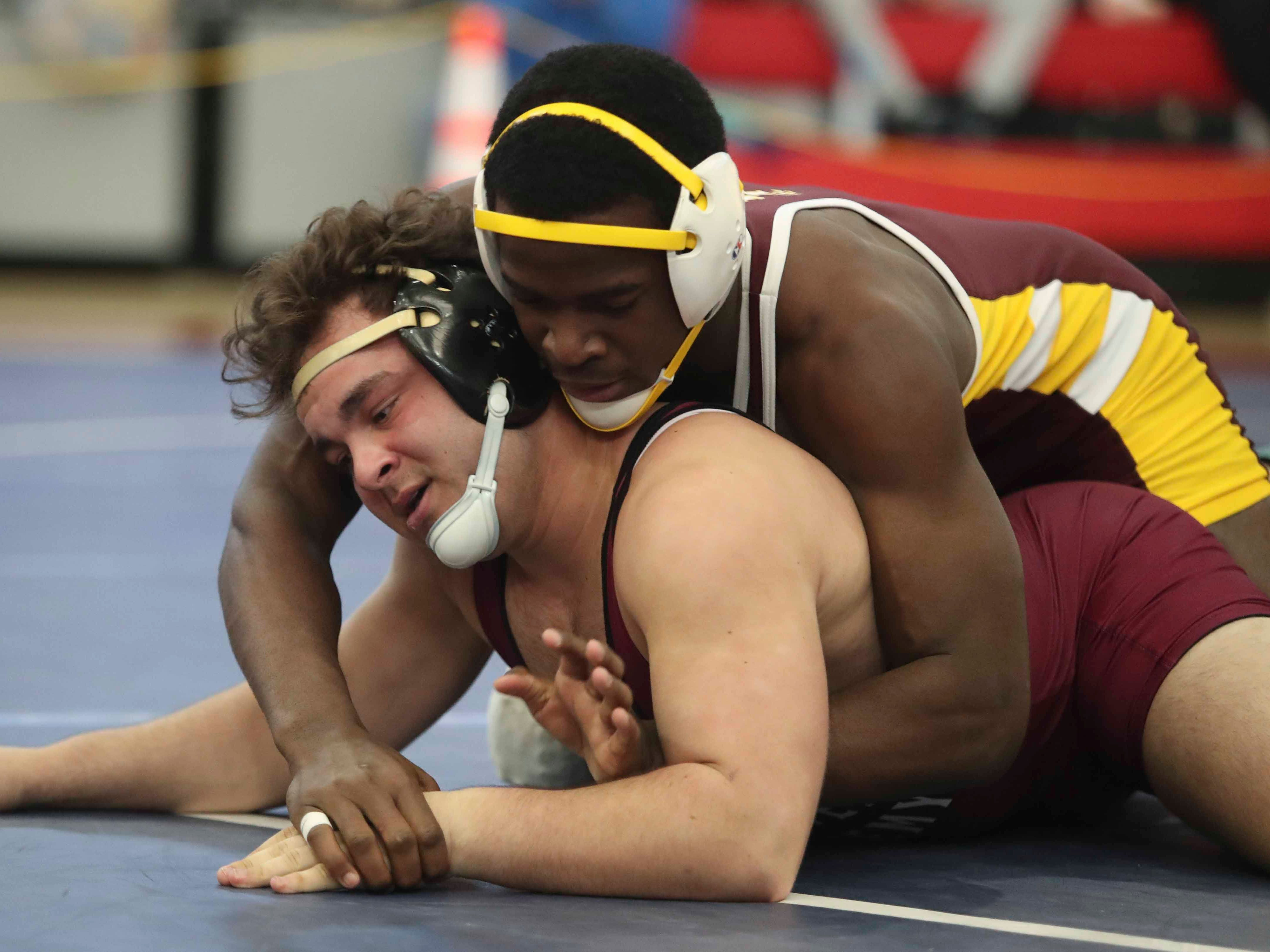 Milford's Bevensky Augustine (top) wrestles Caravel's Luke Duarte before winning at 182 pounds in the final round of the DIAA Division II dual meet championships Saturday at Smyrna High School.