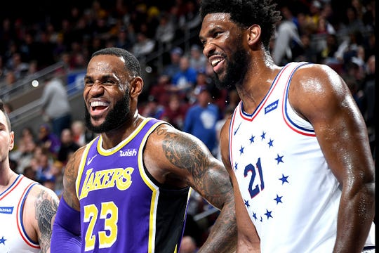 LeBron James #23 of the Los Angeles Lakers smiles with Joel Embiid #21 of the Philadelphia 76ers on February 10, 2019 at the Wells Fargo Center in Philadelphia.