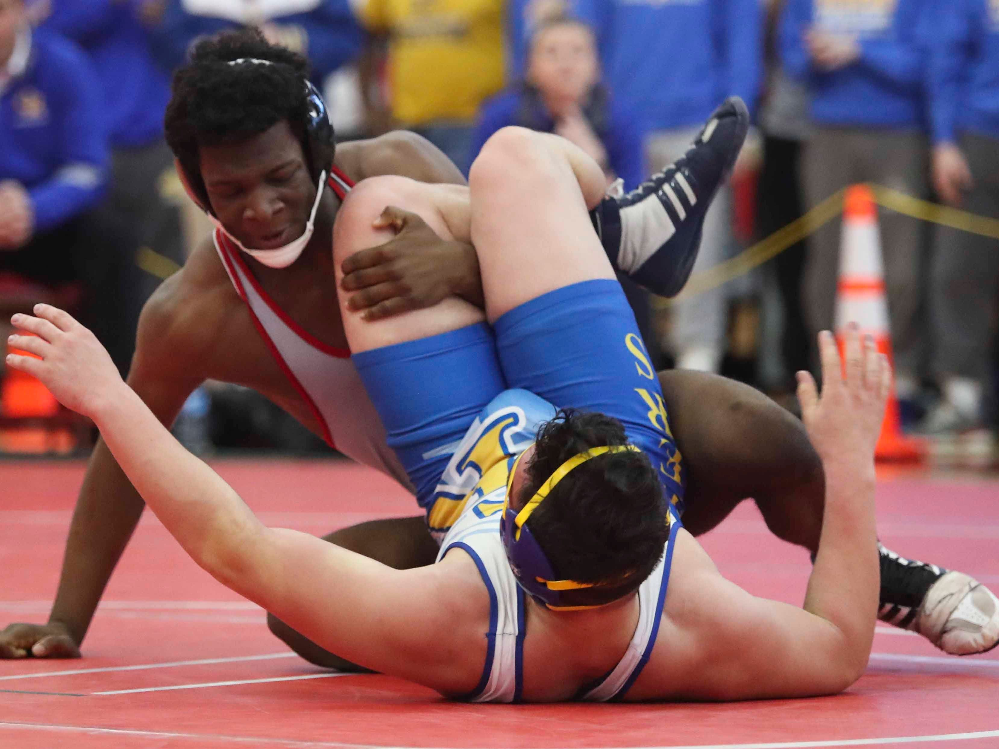 Smyrna's Masen Wilson (left) wrestles before getting a pin on Caesar Rodney's Gavin Boyer at 220 pounds in the DIAA dual meet championships Saturday at Smyrna High School.