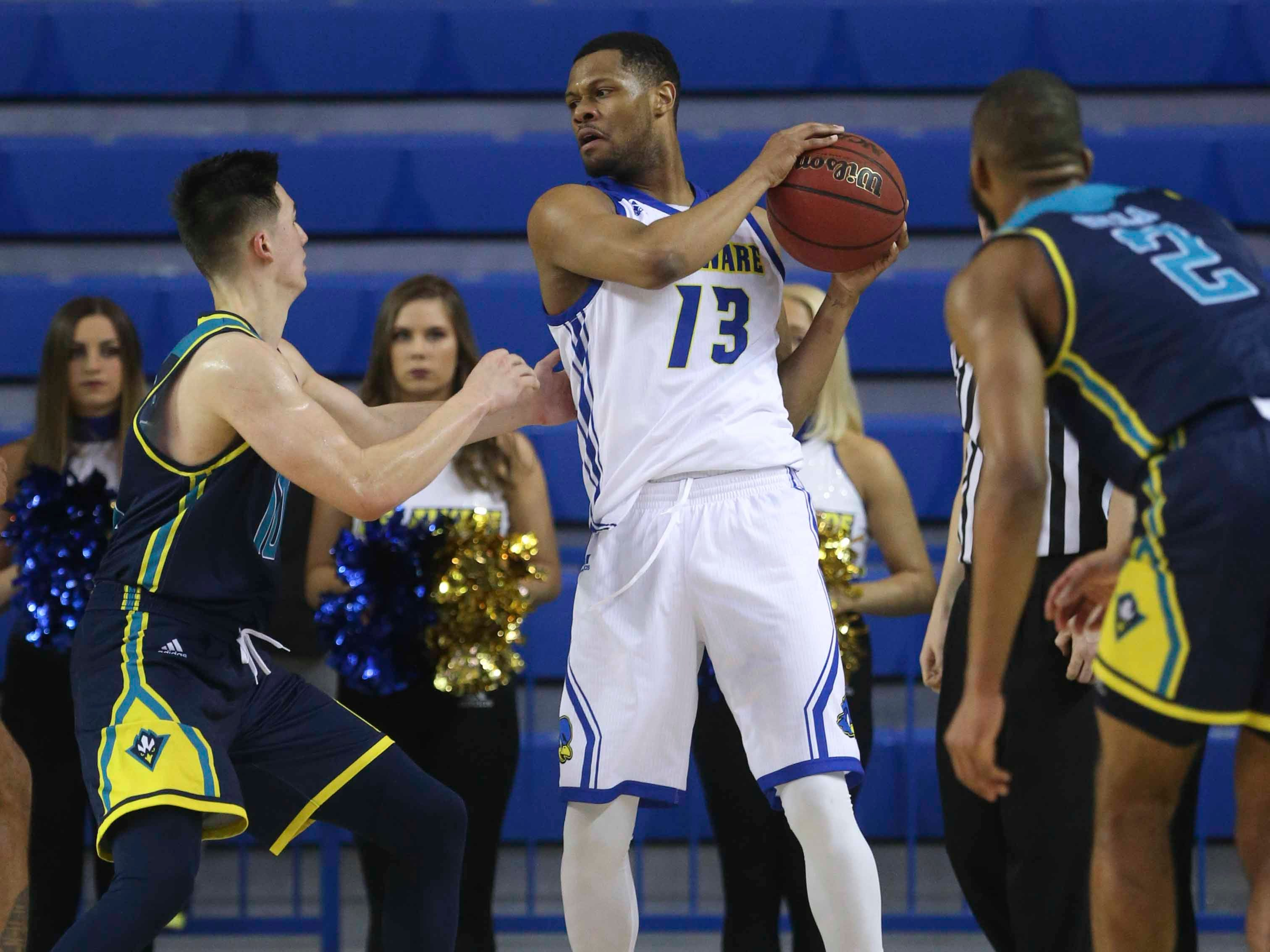 Delaware's Ryan Johnson keeps possession in the final minute as he is defended by UNC-Wilmington's Kai Toews and Jeantal Cylla in the second half of Delaware's 70-66 win at the Bob Carpenter Center Saturday.