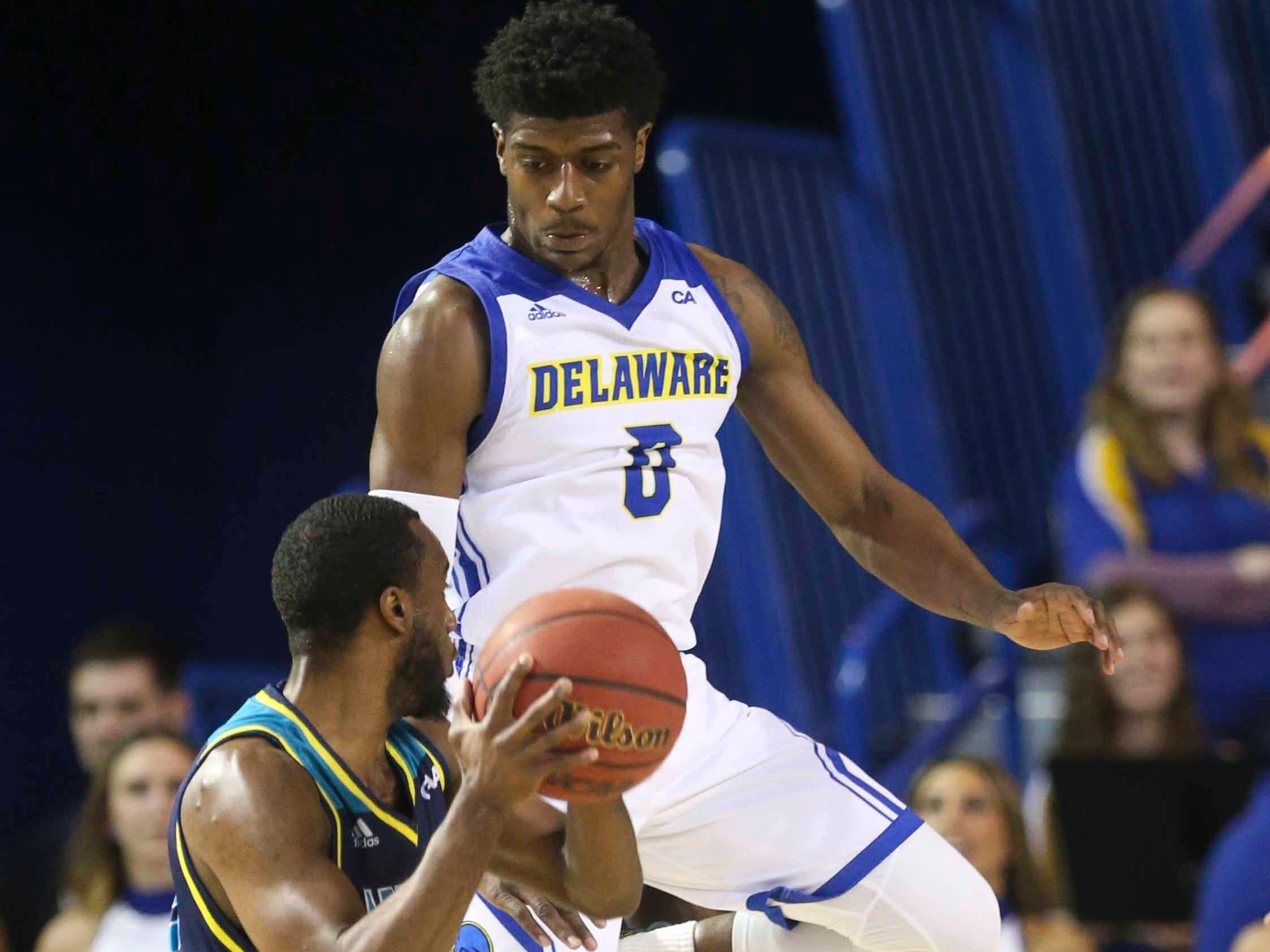 UNC-Wilmington's Ty Taylor draws Delaware's Ryan Allen into leaping on a shot fake in the second half of Delaware's 70-66 win at the Bob Carpenter Center Saturday.