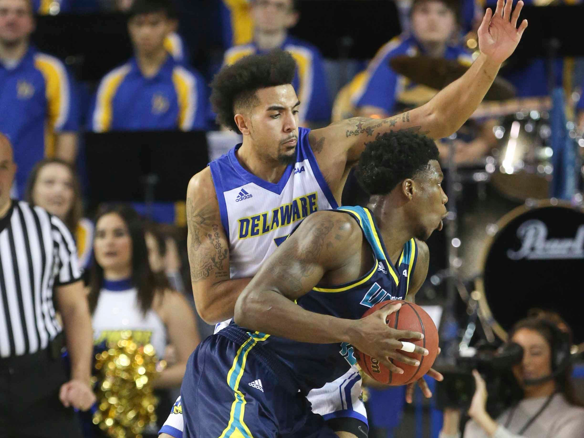 Delaware's Eric Carter (left) defends as UNC-Wilmington's Devontae Cacok pushes to the basket in the second half of Delaware's 70-66 win at the Bob Carpenter Center Saturday.