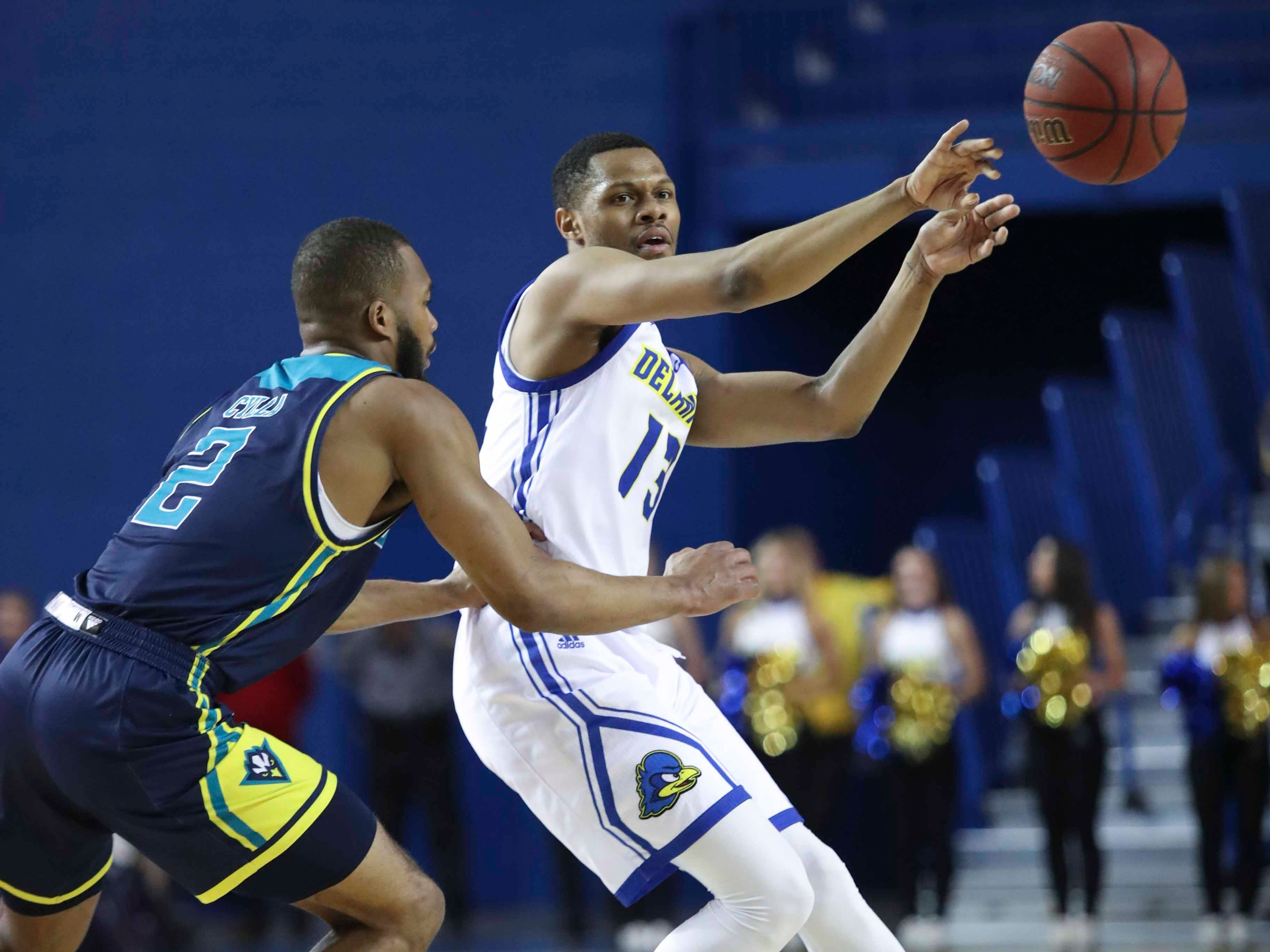 Delaware's Ryan Johnson throws a pass away from UNC-Wilmington's Jeantal Cylla in the second half of Delaware's 70-66 win at the Bob Carpenter Center Saturday.