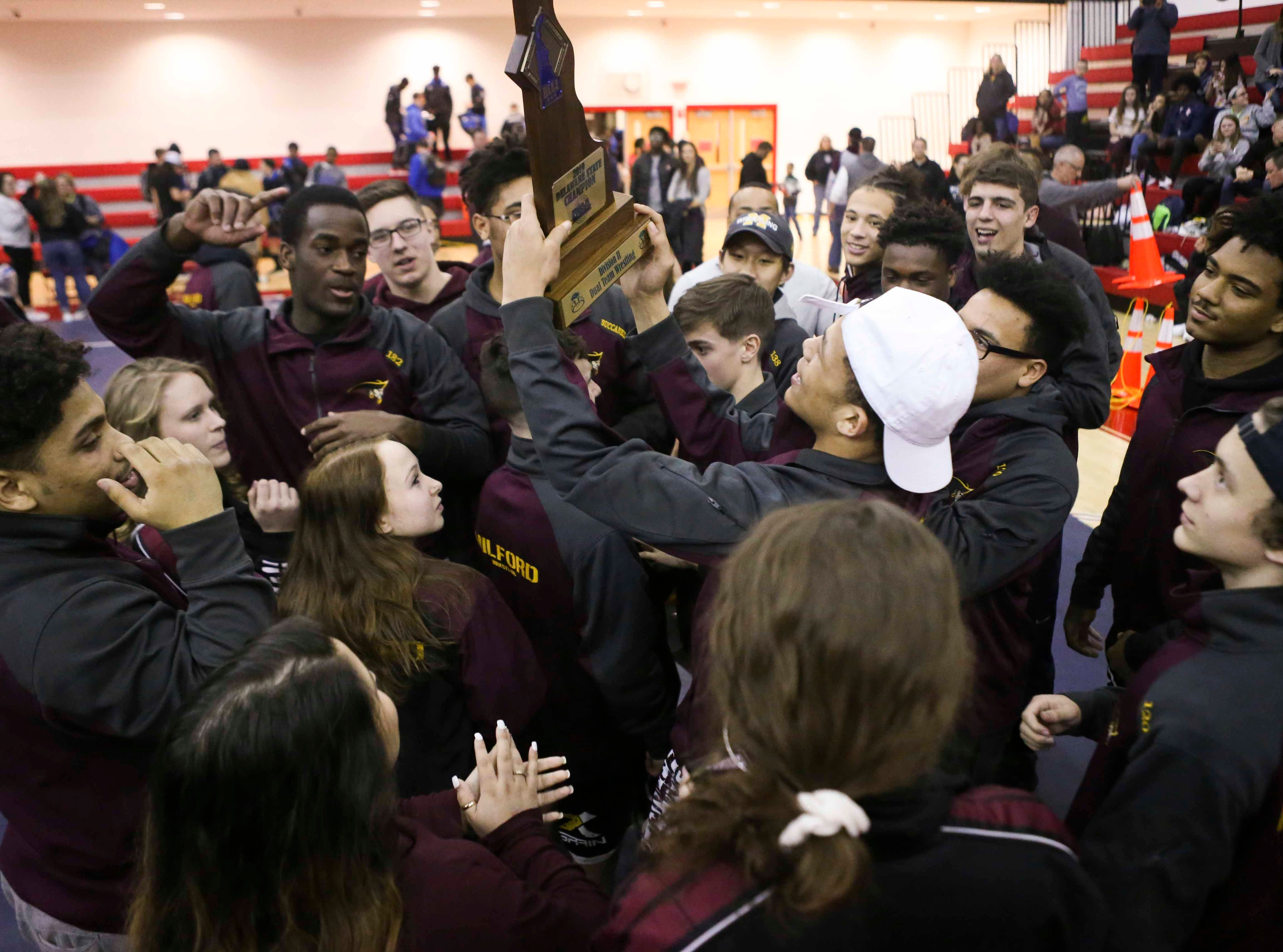 Milford wrestlers celebrate their title in the DIAA state high school Division II dual meet championships Saturday at Smyrna High School.