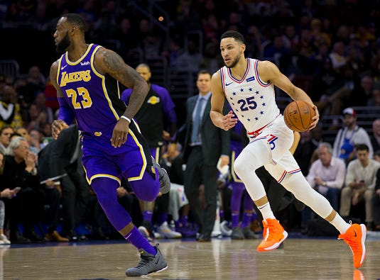 Ben Simmons #25 of the Philadelphia 76ers dribbles the ball up the court against LeBron James #23 of the Los Angeles Lakers in the second quarter at the Wells Fargo Center on February 10, 2019 in Philadelphia.